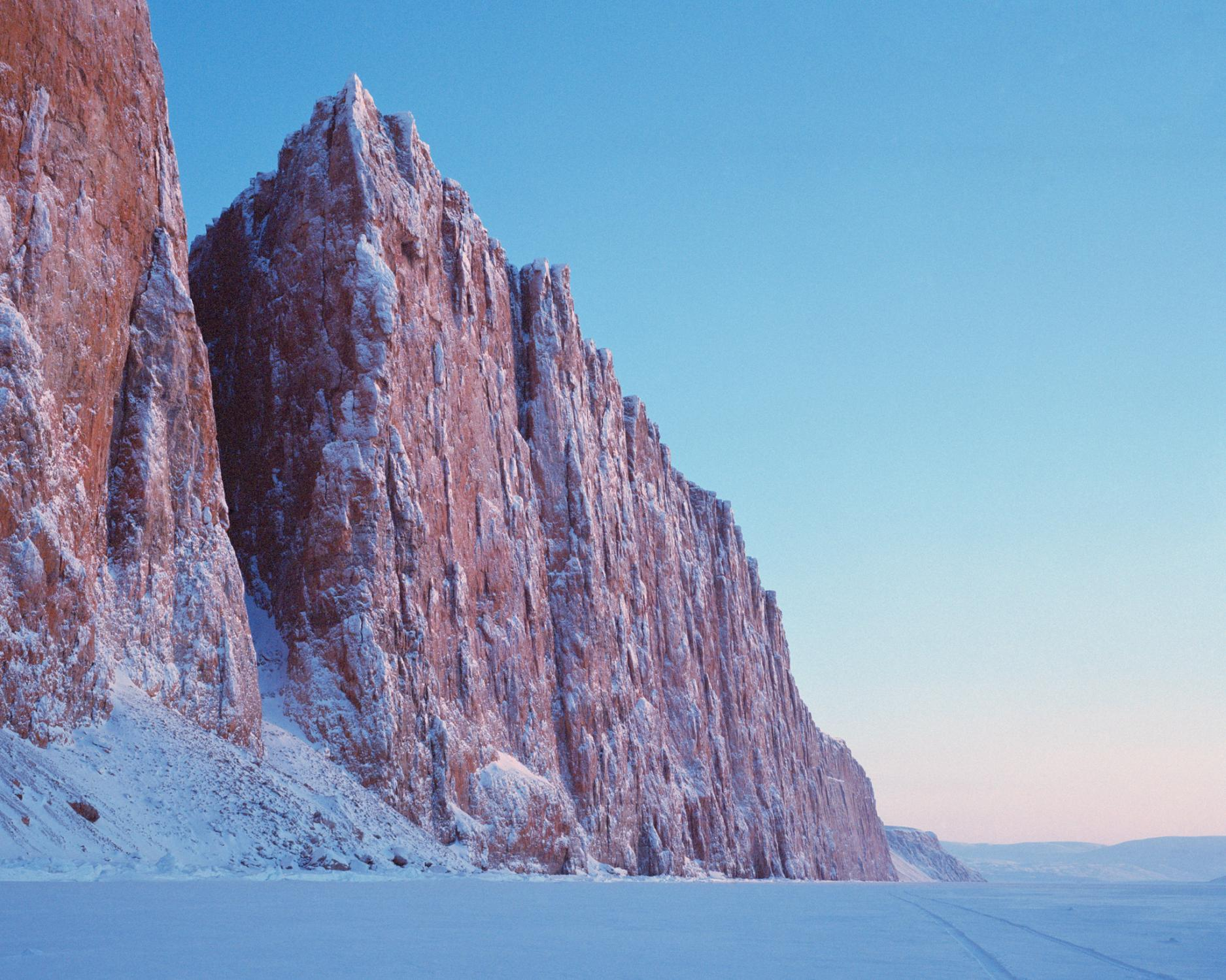 Dramatic cliffs rise from the sea ice just outside of Arctic Bay.