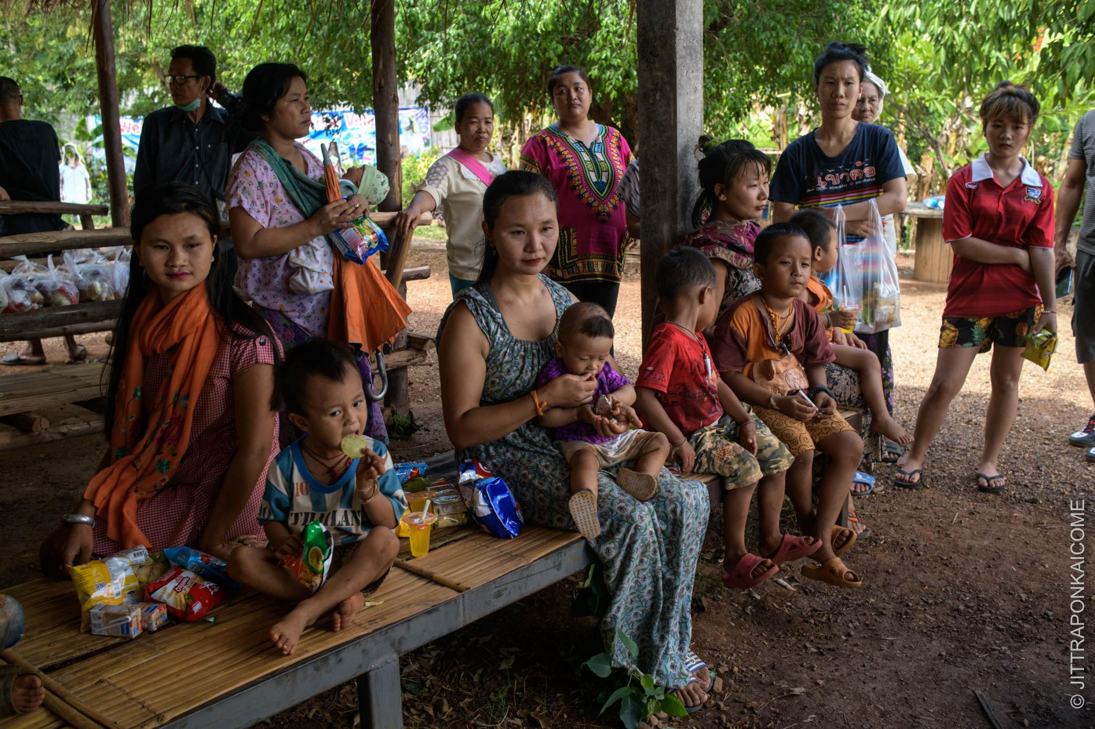 In a tourist hill tribe village in Mae Tang, multiple ethnics hill tribes including Karen Long Neck are waiting to received food handouts. Chiang Mai, Thailand.