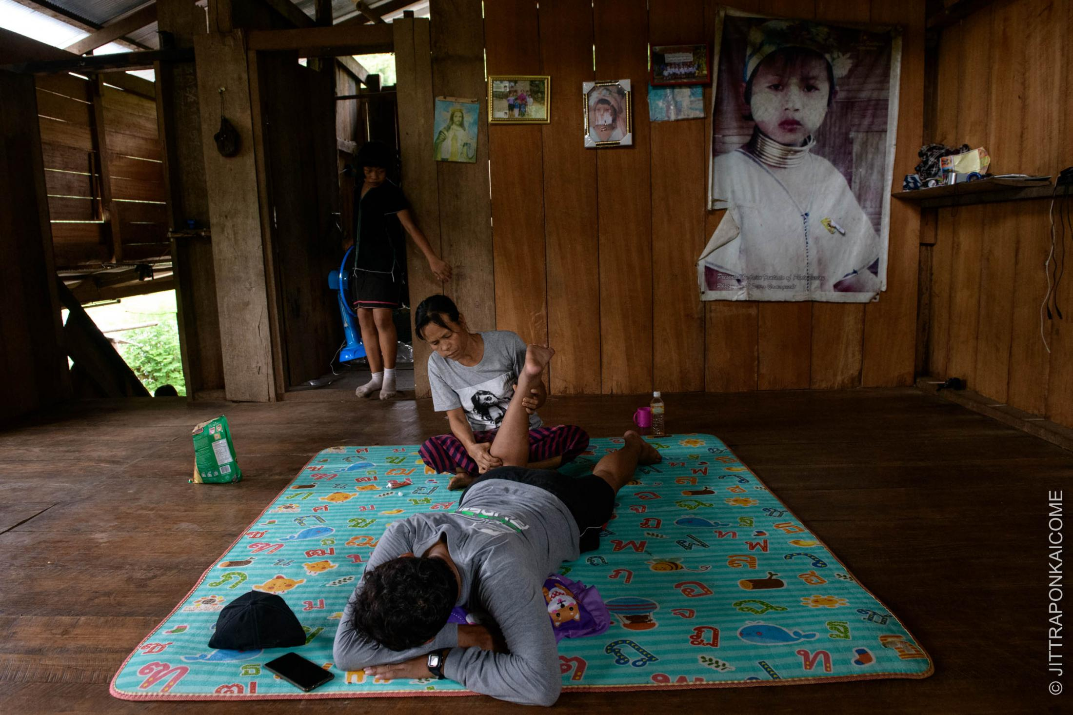 During the village lockdown at Huey Pu Keng, a Kayan Long Neck woman is giving a traditional massage to a local teacher.
