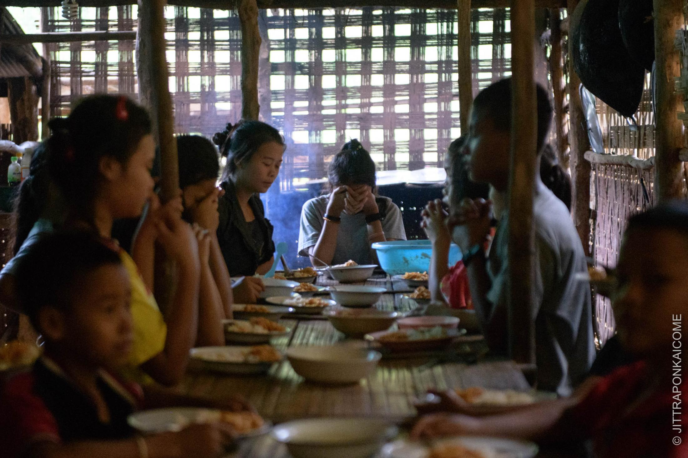 At Baan Nai Soi, a Kayan Long Neck village. Most families are having financial difficulties due to no tourists, and there are only a few options to seek for jobs that they can do during the economic downturn of the COVID-19. Kids are praying before meal - Mae Hong Son, Thailand.