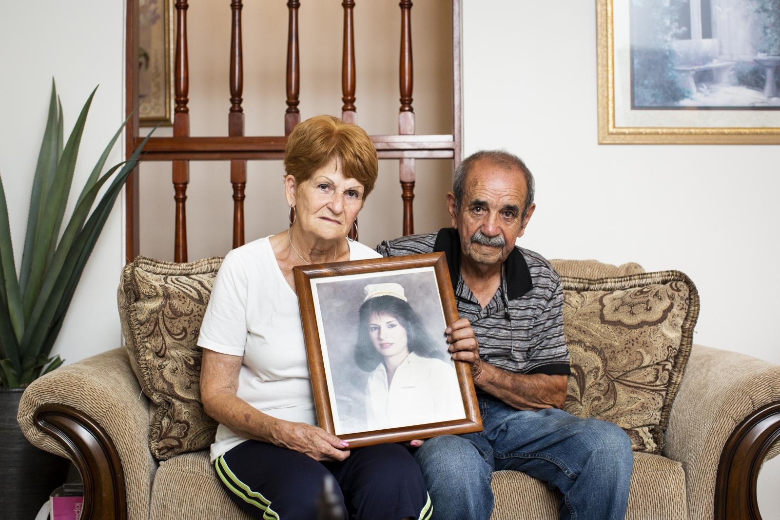 Nereida Maldonado Molina, 74, and Sotero Viera Gonz�lez, 80, pose for a portrait at their home in Lares, P.R., on October 2, 2018. The remains of their daughter, Madeline Viera Maldonado (photo in frame), had rested in the Lares Municipal Cemetery since she was murdered in a carjacking in 1992, until her grave was damaged by the hurricane. On January 12 of this year the couple had to re-bury their daughter in a private cemetery in Camuy, a neighboring town. They had to purchase a new lot and pay for all move and transportation of the remains. The Federal Emergency Management Agency denied the family any aid for the process. Now that Madeline's tomb is located farther from her parents, the couple is unable to visit it as often as they did. The town's cemetery has been closed for over a year since hurricane Maria caused land slides and damaged or unearthed 1,779 tombs according to the town's mayor, Roberto Pag�n Centeno. Family members are not allowed to the area where their loved ones rest, something that has caused altercations at the gate with the administration. Since no regular funeral is allowed on the cemetery some people have resorted to burying their loved ones in nearby towns to abide by their traditions. The Department of Health of Puerto Rico closed the location until further notice, and while a new land was acquired to create a new cemetery, there is no clear plan to attend the issue of the hundreds of remains that have been affected.