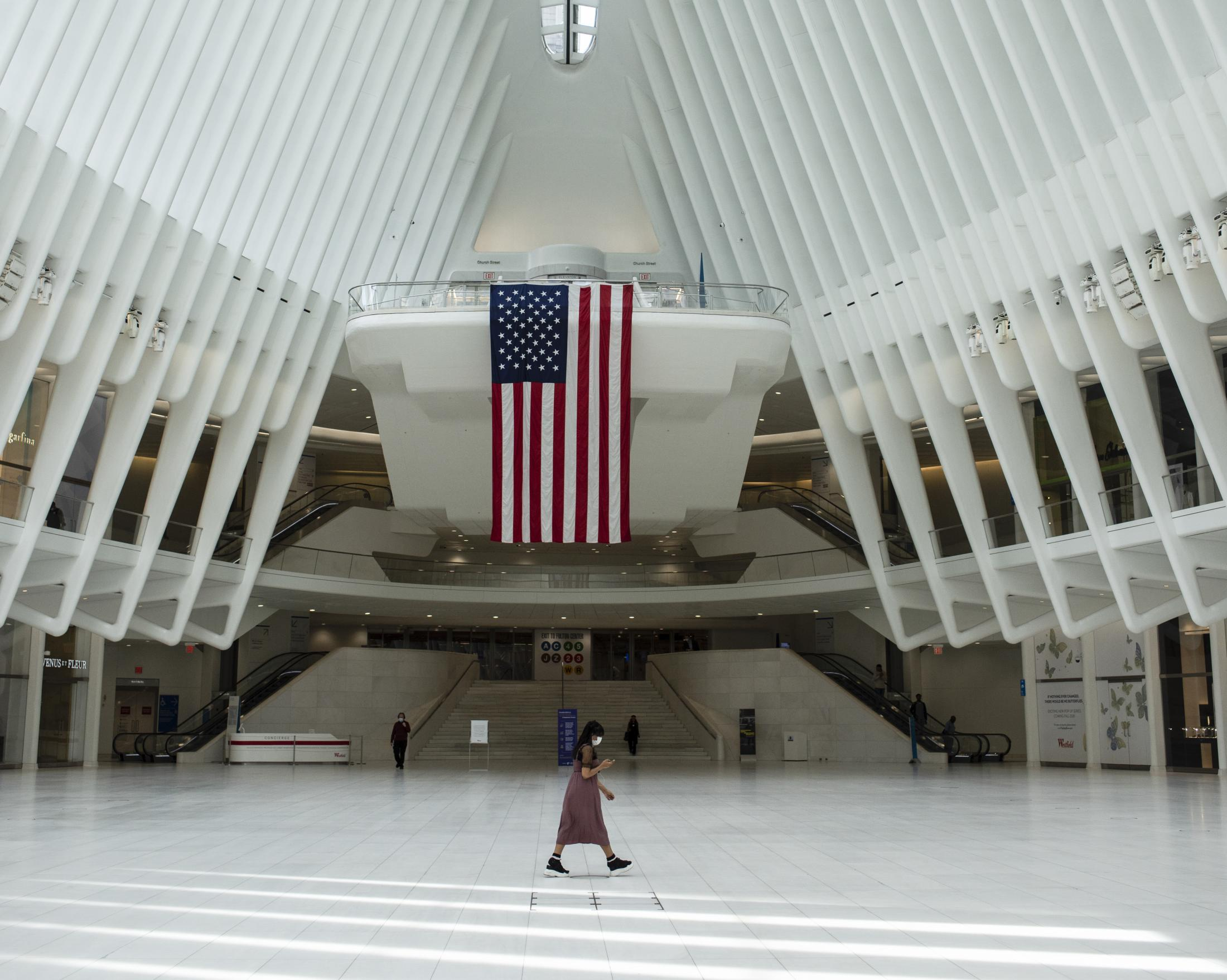 A woman walks over to an almost empty WTC PATCH train station, in Manhattan. During the first days of the pandemic, the governor of the State of New York, Andrew Cuomo, declared a state of emergency, paralyzing the biggest city in the United States.