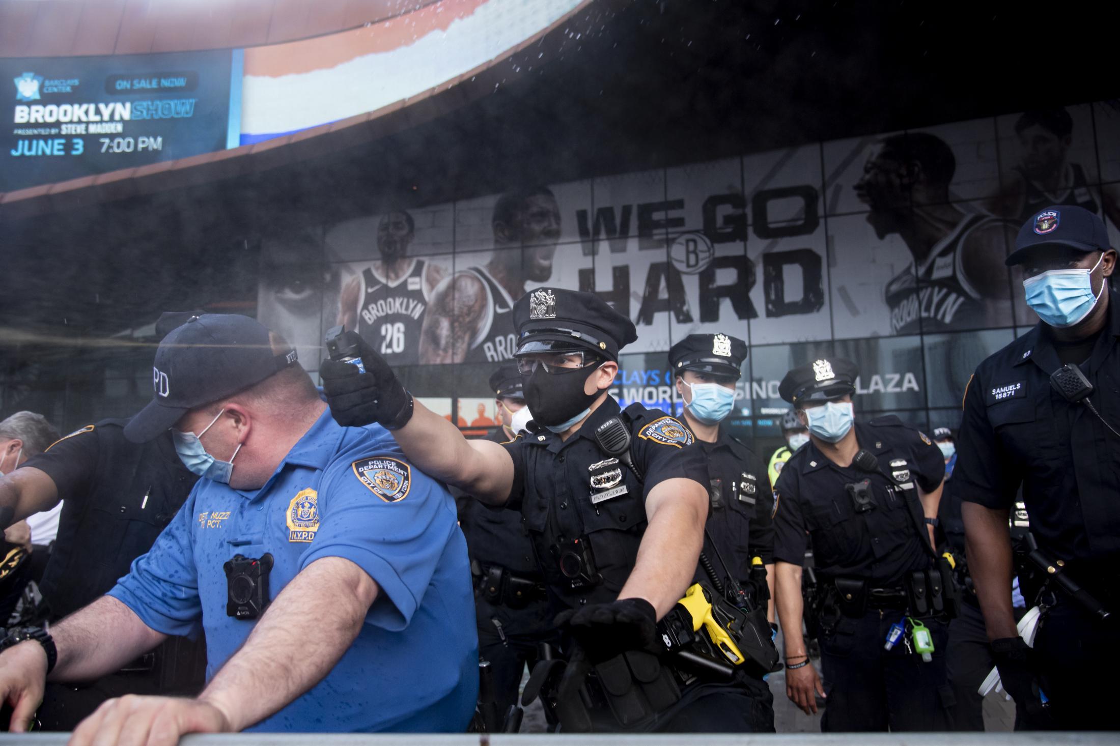 Un policía de NYPD rocía con spray de pimienta a protestantes reunidos en el Barclay's Center, Brooklyn, exigiendo la reducción del presupuesto policial, en incremento de políticas públicas en servicios sociales.