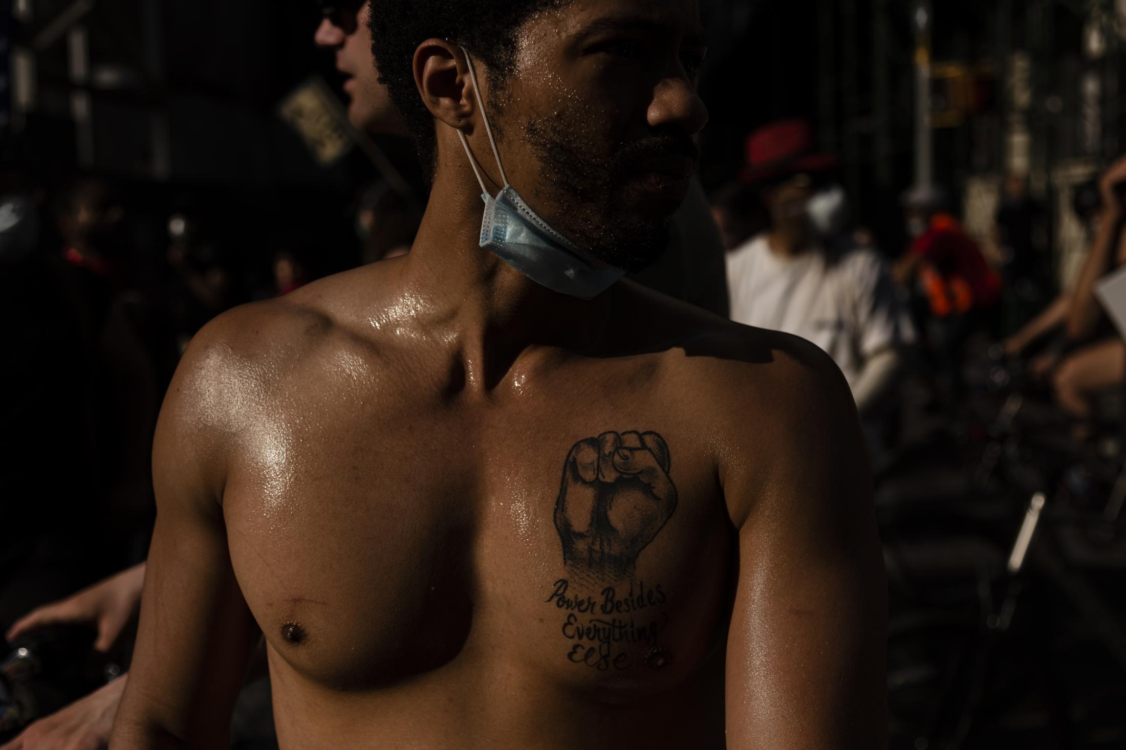 Un jóven adherente al movimiento BLM, muestra un tatuaje en su pecho que traduce 'Poder Ante Todo', durante una protesta en Brooklyn, Nueva York. Durante los meses más crudos de la pandemia en ciudad, las calles volvieron a la vida luego del llamado al apoyo en contra la brutalidad policial en Estados Unidos.