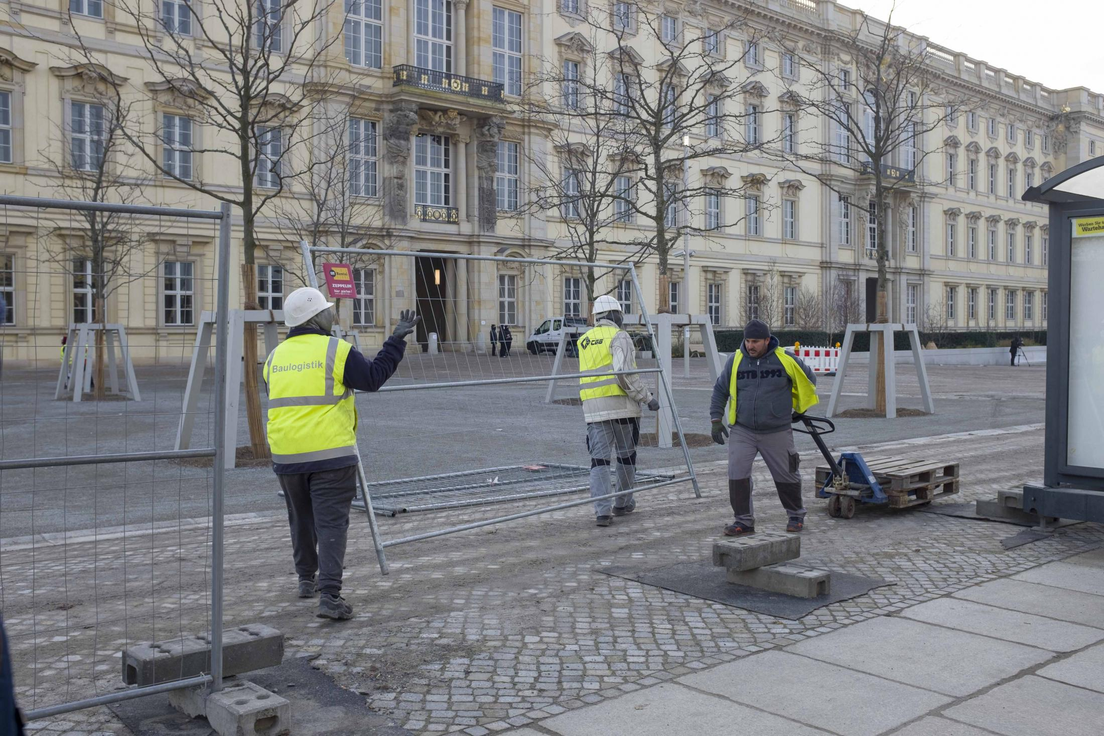 Workers take down the construction hoarding around the reconstructed Berlin Palace. After 20 years of debate in the 90s and 2000s, and eight years of construction time, the Humboldt Forum museum, which is housed in the building, was inaugurated yesterday in a virtual ceremony. At a total construction cost of 595 million euros, it is the second major joint construction project of the federal and state government that is finished this year. The other one is Berlin's BER airport, which opened in November after becoming famous for its massive delay in construction and equally massive spike in costs. While the new airport is currently operating way below its capacity due to the Coronavirus pandemic, the museum will remain closed for visitors for the time being. Berlin, December 17, 2020.