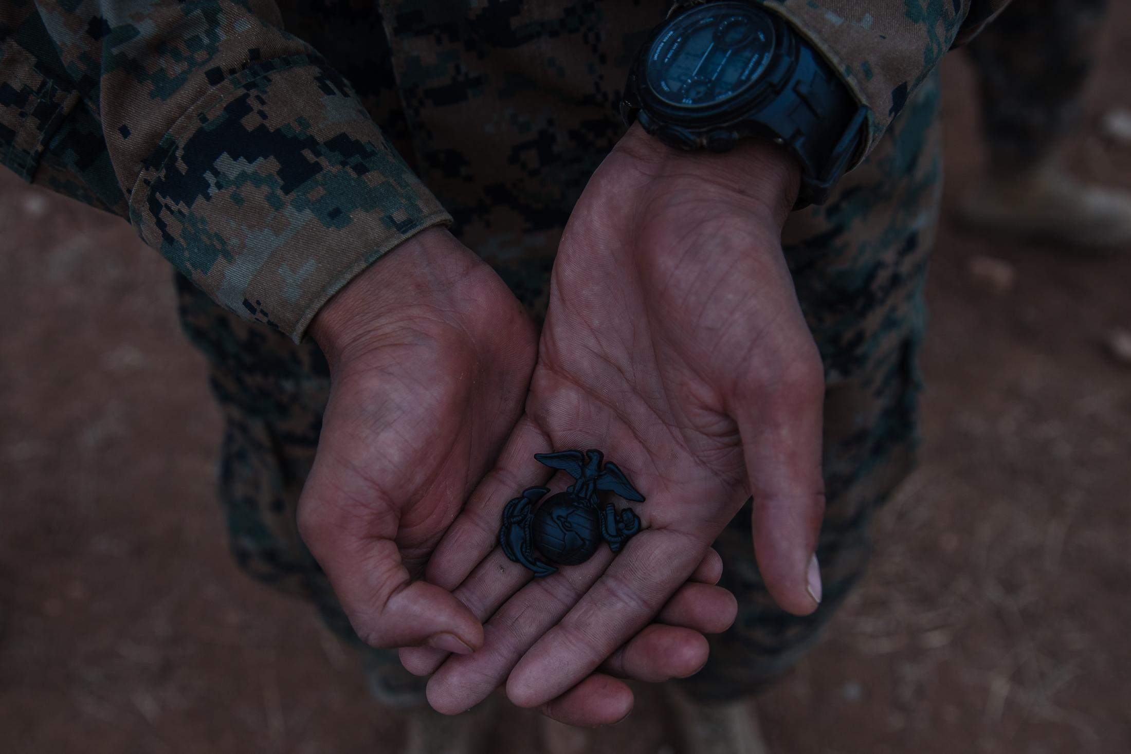 A recruit holds his Eagle, Globe and Anchor pin.