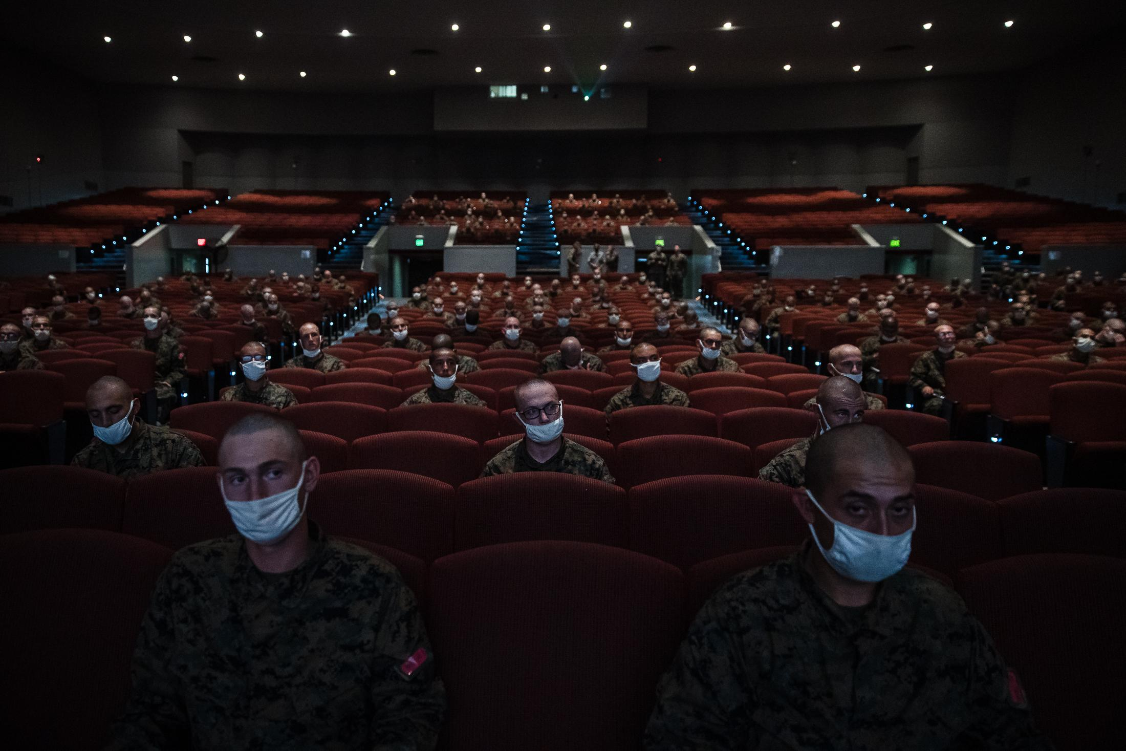 Recruits sit in the auditorium for class wearing face masks with empty seats in between them due to Covid-19 at the Marine Corps Recruit Depot San Diego.