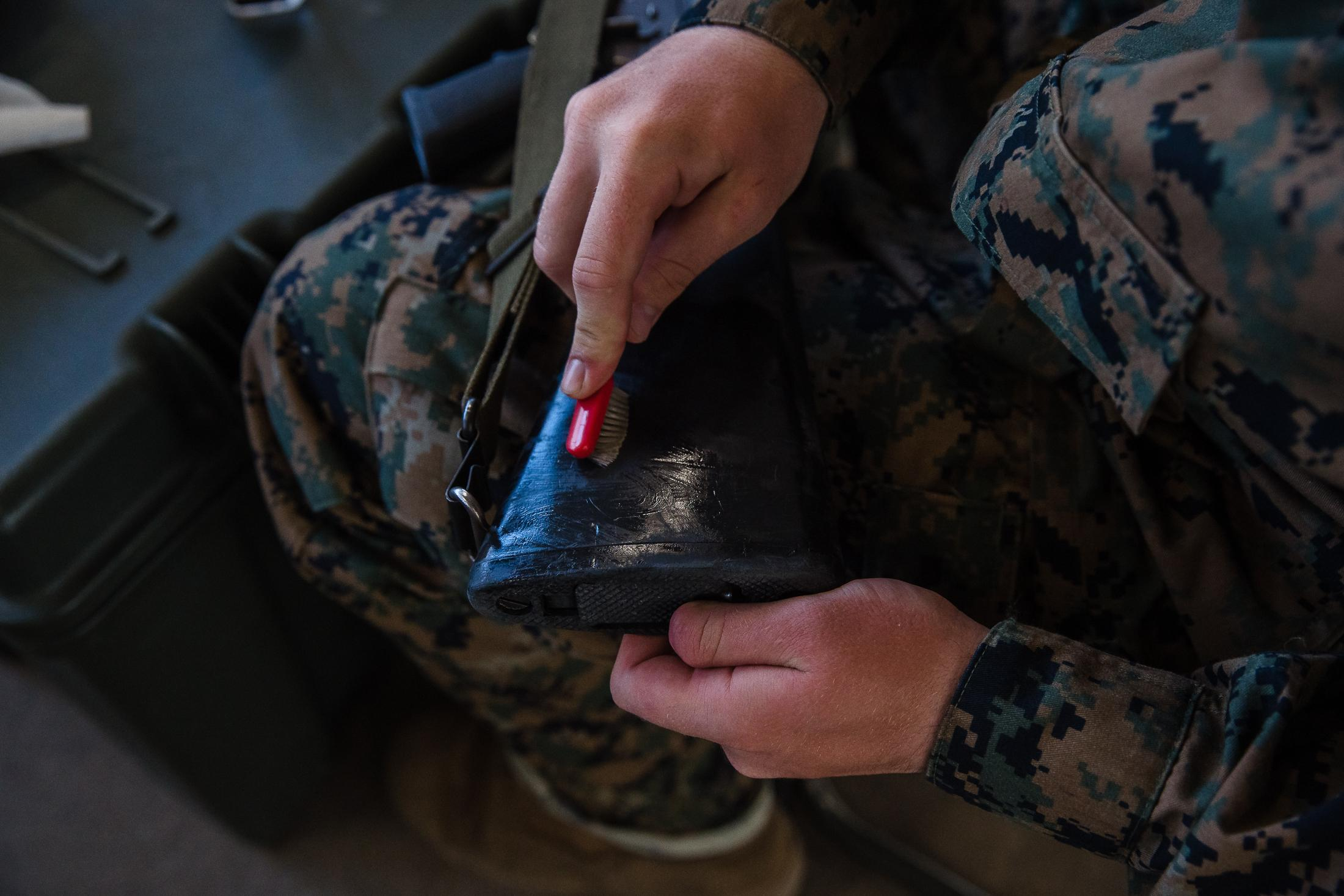 A young recruit cleans his gun inside the barracks using a toothbrush at the Marine Corps Recruit Depot.
