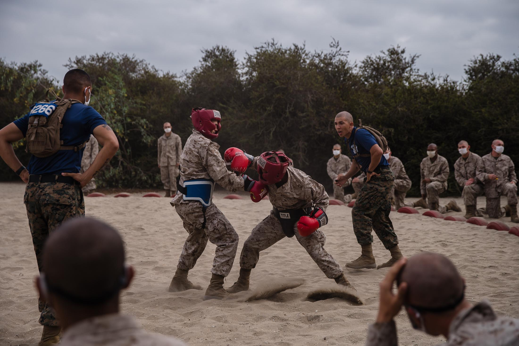Men spar on the sand at the Marine Corps Recruit Depot San Diego, while the other recruits watch wearing face masks due to Cover-19.