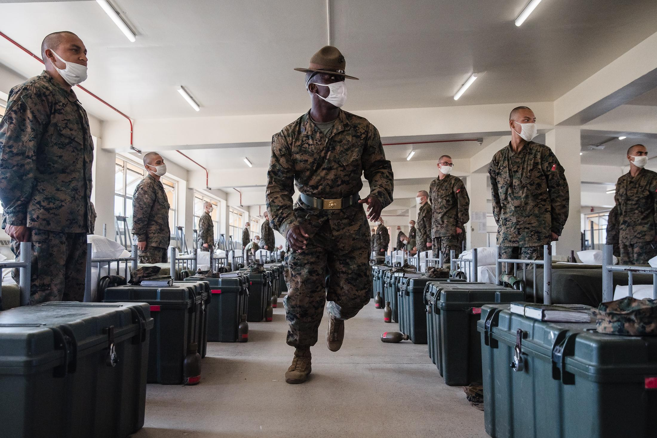 Sergeant Kirk Broxton walks through the barracks checking if beds are made correctly at the Marine Corps Recruit Depot.