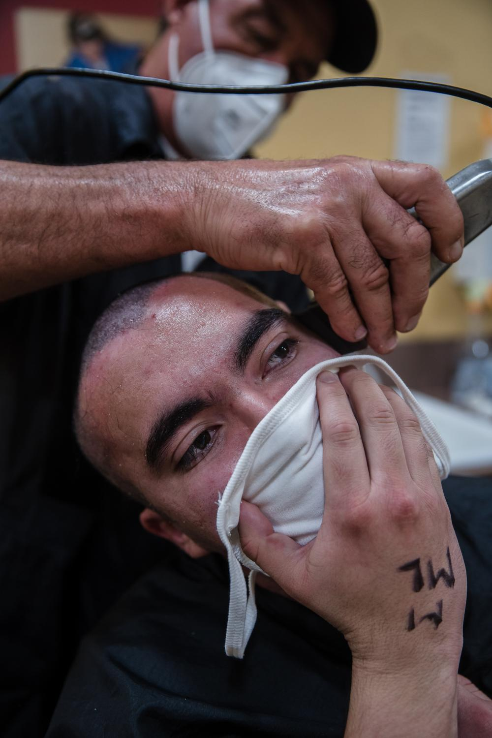 Gerard Ortiz, 24 years old from Pueblo, Colorado gets his head shaved at the barber shop after arriving at the Marine Corp Recruit Depot in San Diego, California on October 8, 2020. Ortiz feels the two weeks in quarantine have helped him get ready to be in the right mindset.