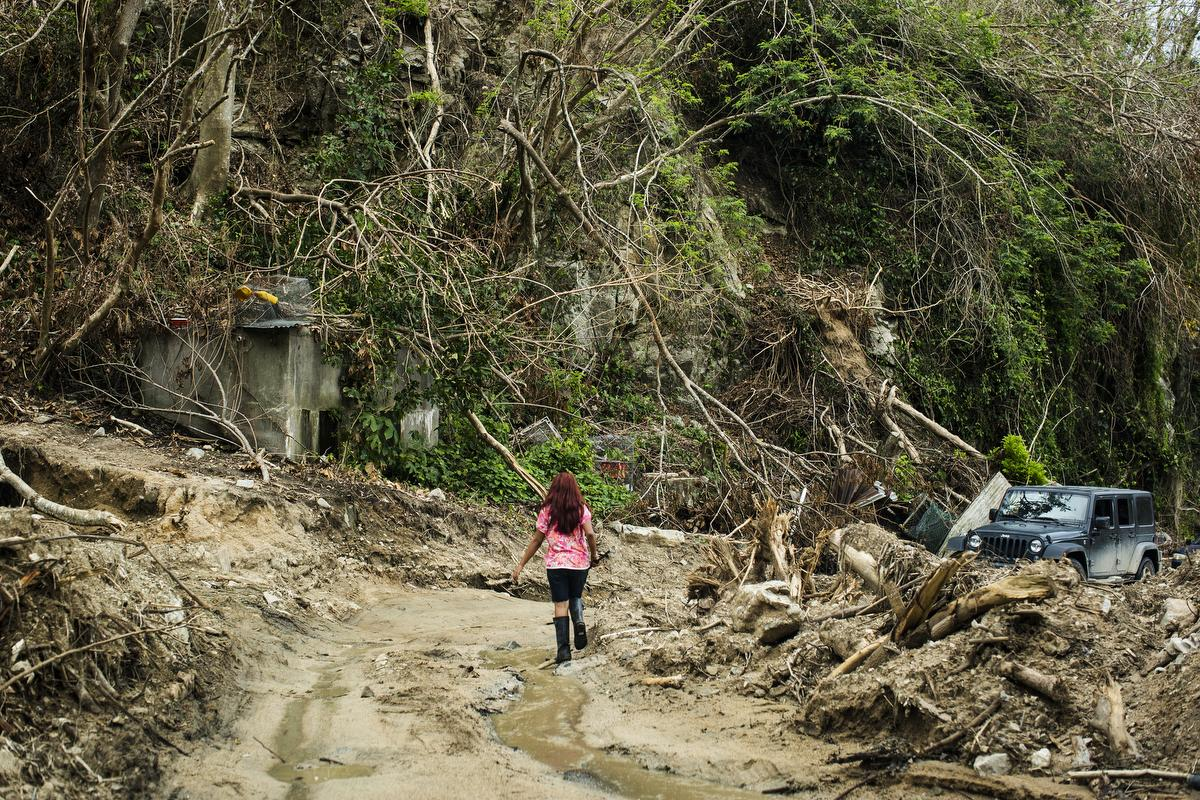 A girl in the mountainous central city of Utuado walks towards what used to be her home. A small creek nearby over flowed during the storm, eroding the road and pushing debris through the walls. The family fled the structure during the storm and took shelter in a nearby house that was empty.