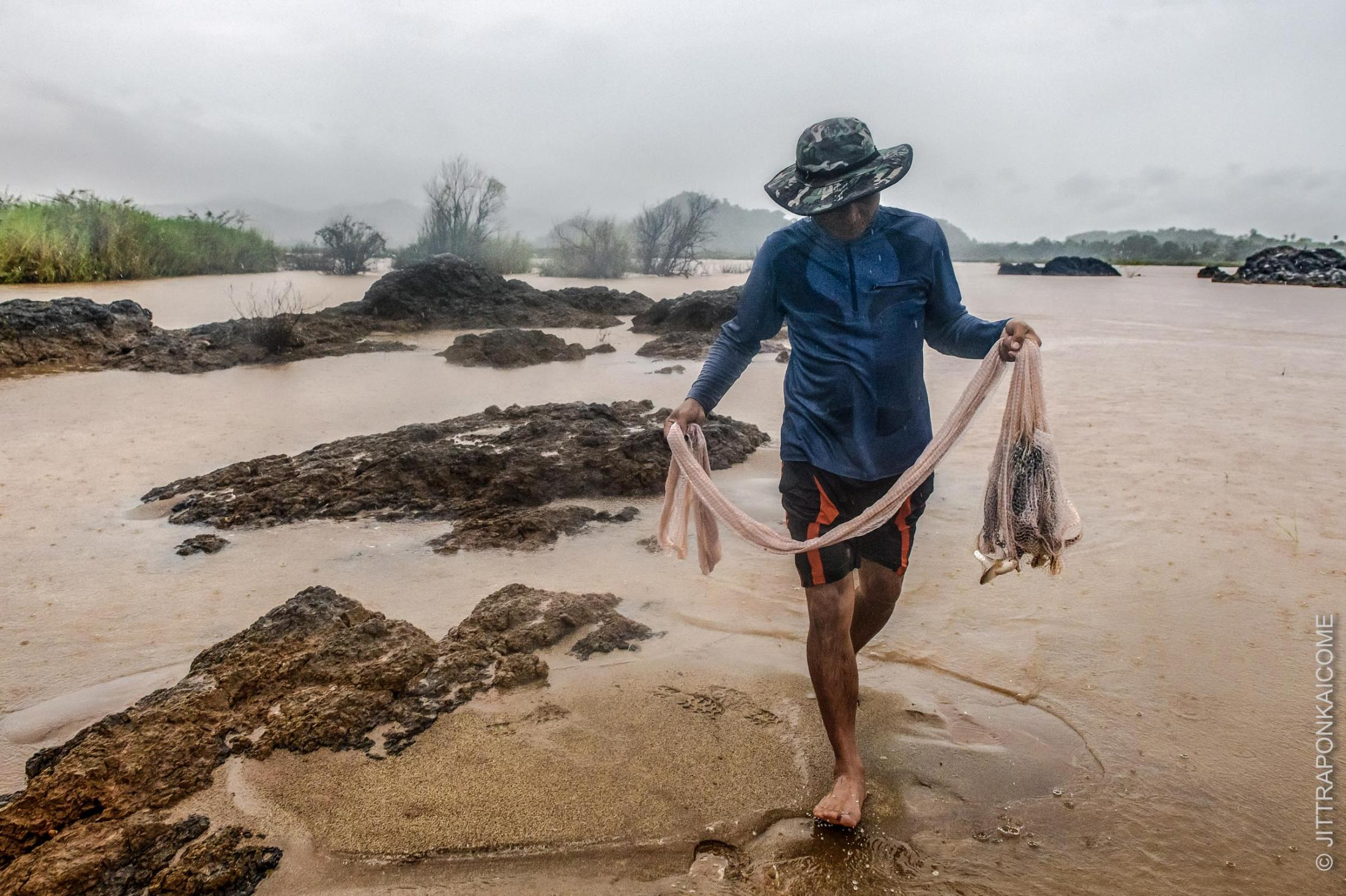 During the rainy season, a fisherman tries to catch fish in the rapids amidst the rocks, raised due to the low water level of the Mekong River. These historically low levels are caused by the unexpected control of water inflow from upstream dams in China and Laos on the Mekong River. Sangkhom district, Nong Khai, Thailand – August 2, 2020.