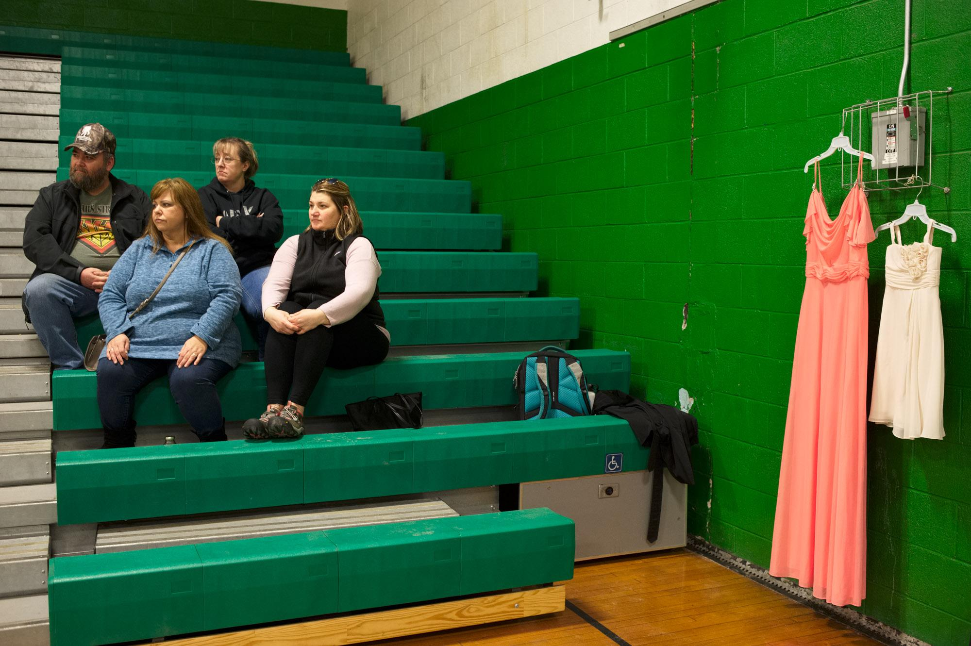 Parents watch as participants of the 63rd Apple Blossom Cotillion do their first rehearsal in the gym of the Riverside School. On the right a display of the dresses the older and younger girls will be wearing during the dance show, in the colors coral pink and creme. The color of the dresses changes every year, in 2017 it was red, in 2018 yellow. Springfield, Vermont, USA. January 2019.