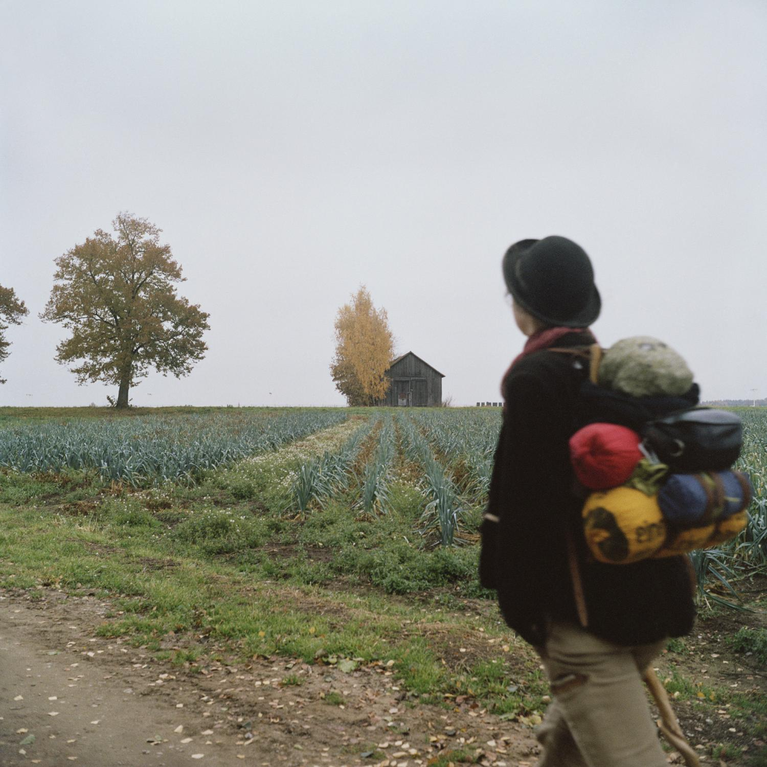 Lisa, a ceramist, walks in the outskirts of Nuernberg, as she follows the group accompanying Gudrun on her departure, ahead of her trip towards Saint Malò in France, where she will try to get a job on a sailing boat heading South America.