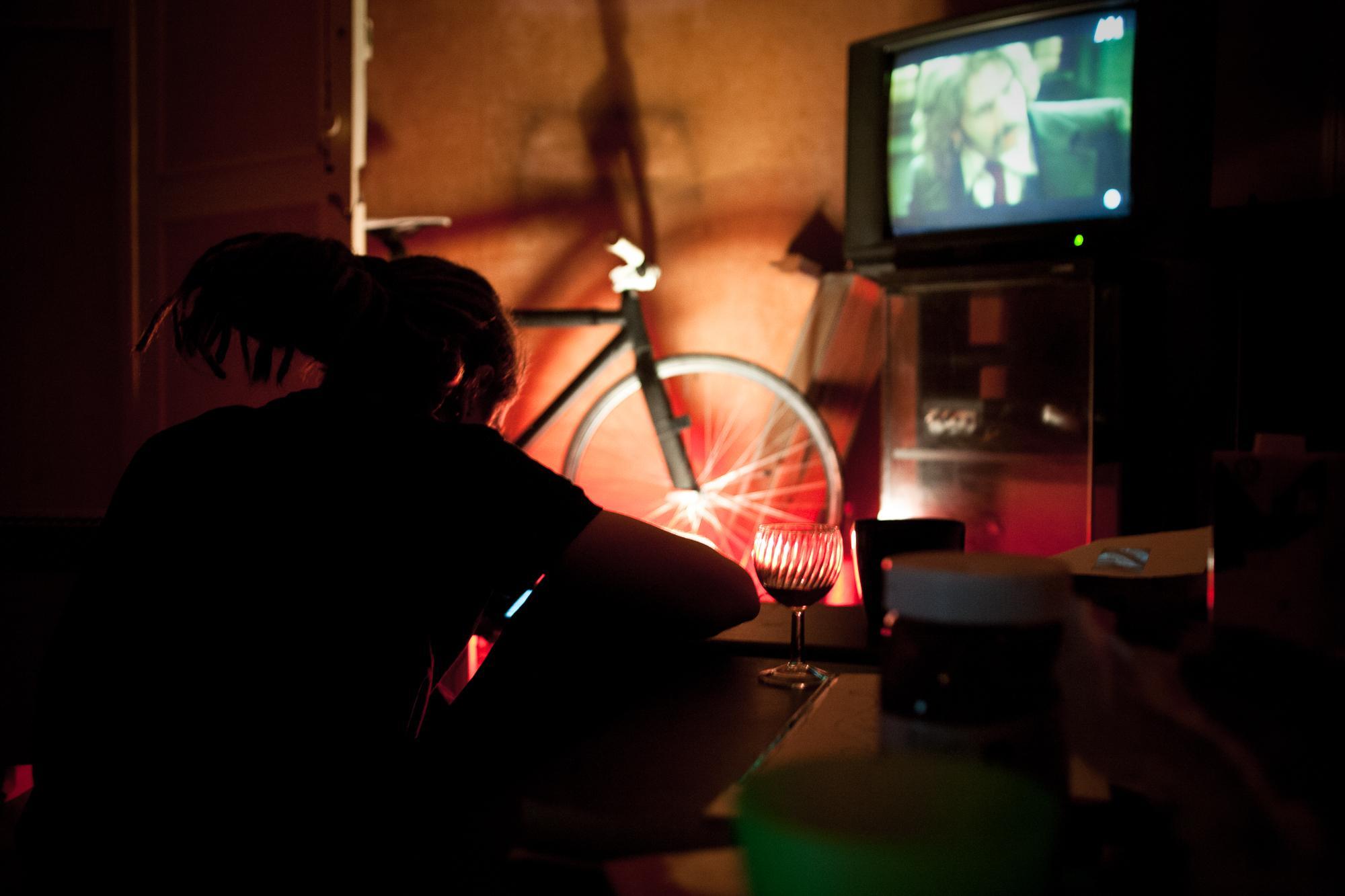Inside the Mabo squat. In his room, Bobby plays on his phone wile watching TV. Dans le squat du Mabo. Dans sa chambre, Bobby joue sur son téléphone en regardant la télévision.