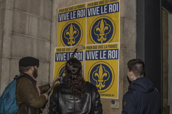 Des militants, dont Guillaume aÌ€ gauche de l'image réalisant un collage d'affiches, dans les rues de Paris.  Activists, including Guillaume on the left of the picture making a poster collage, in the streets of Paris.
