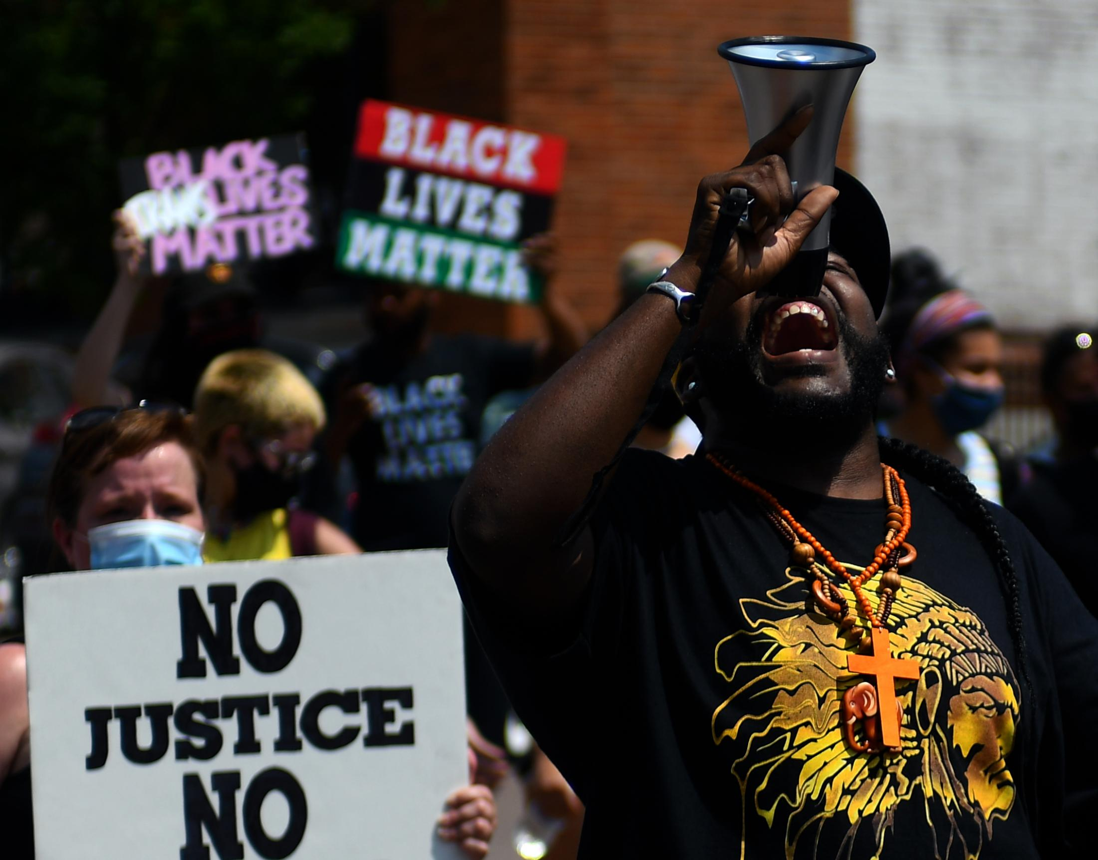 """Roy Lovelady shouts into a megaphone while marching on Sunday, June 7, 2020, in Columbia, Missouri. Lovelady is a local business owner, he helps organizing and leading peaceful protests for """"People's Defense"""", a Columbia social justice group."""