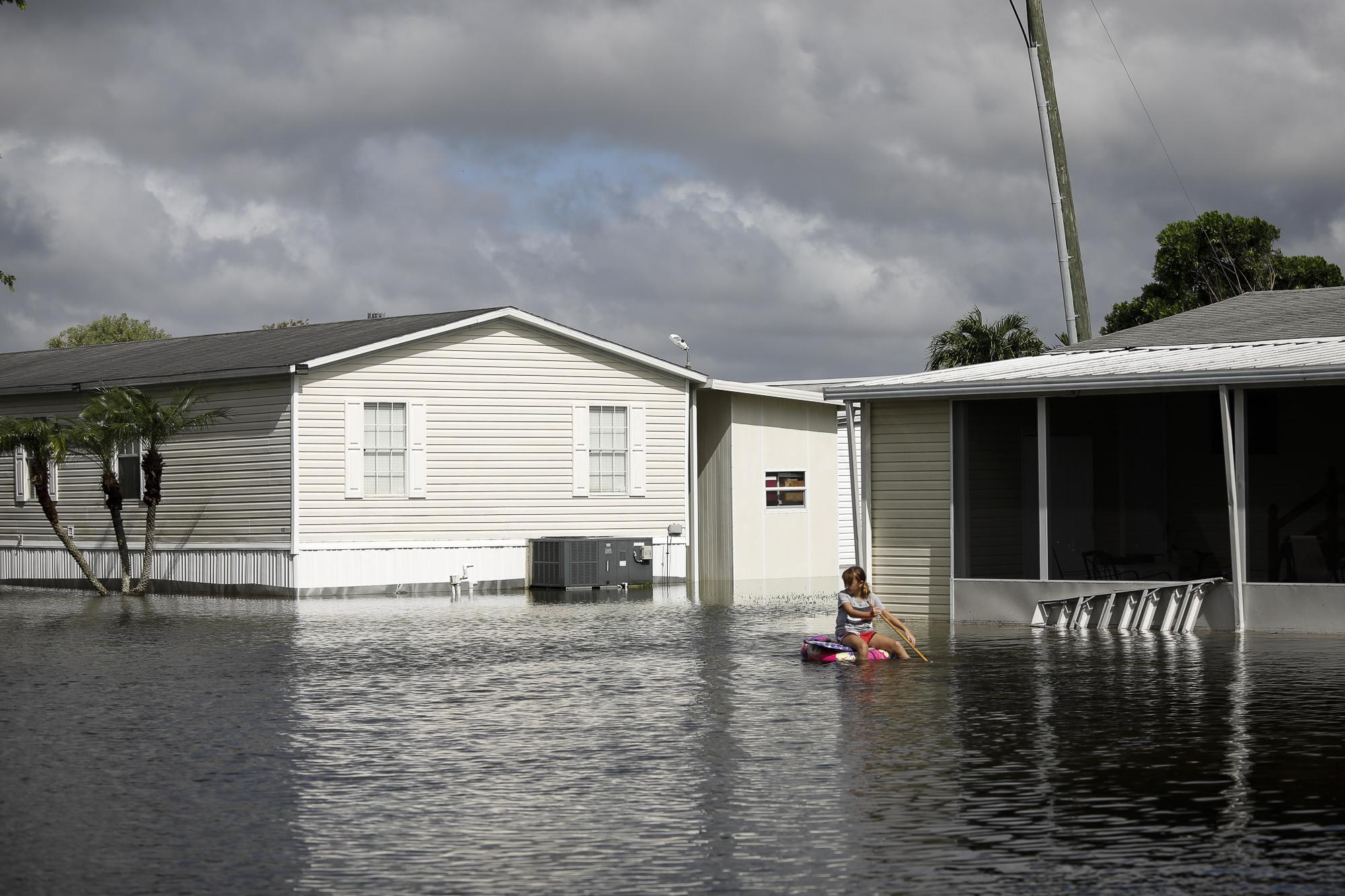 A girl pushes a float boat in floodwaters caused by Storm Eta in Davie, Florida, U.S., November 9, 2020. REUTERS/Marco Bello