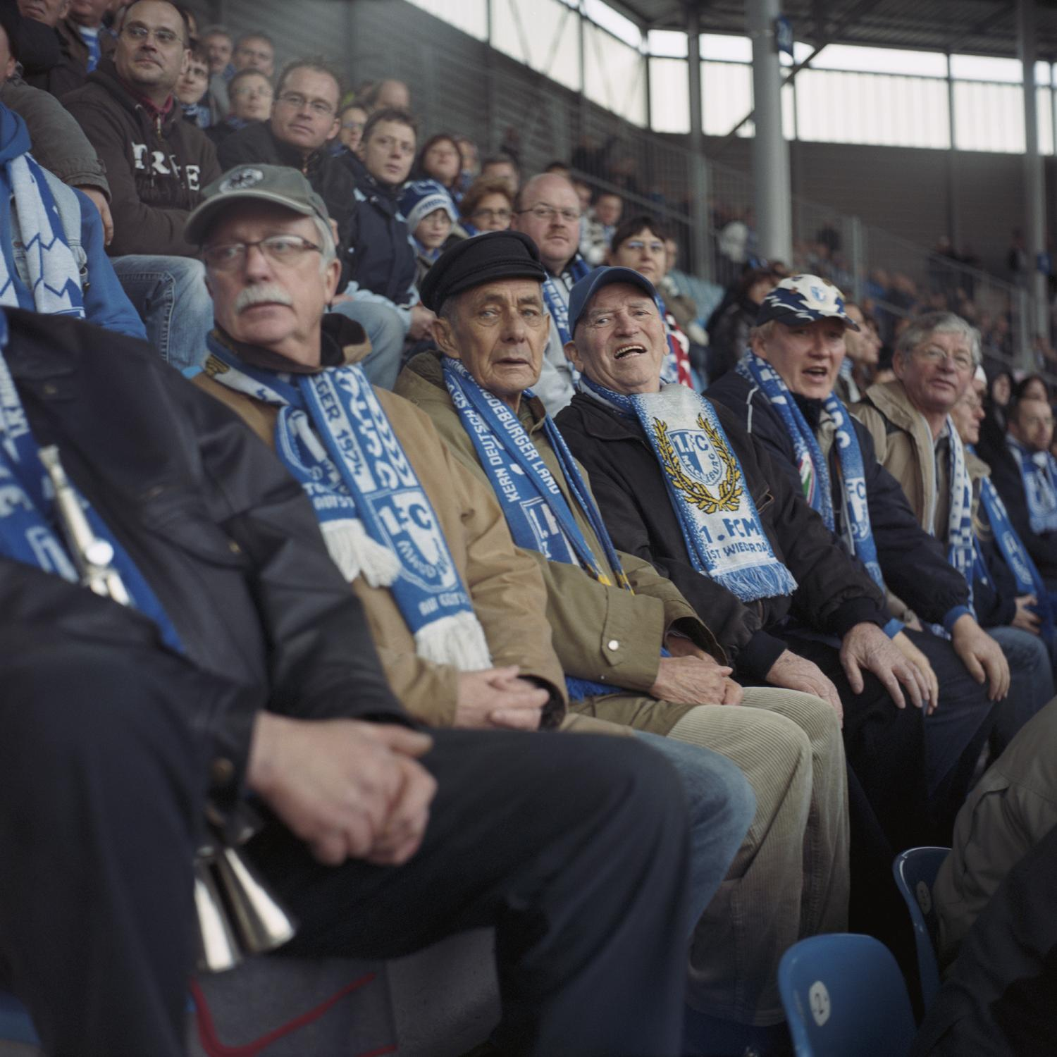 "A group of older supporters focus on the game 1. FC Magdeburg v Tennis Borussia Berlin (7:0) in the stadium in Magdeburg. The team used to be the most successful one in the GDR and got a legendary ""UEFA Cup Winners' Cup"" in 1974. Thanks to this glorious past 1 .FCM still has enjoyed a huge amount of supporters during good and bad times after the fall of the Wall."
