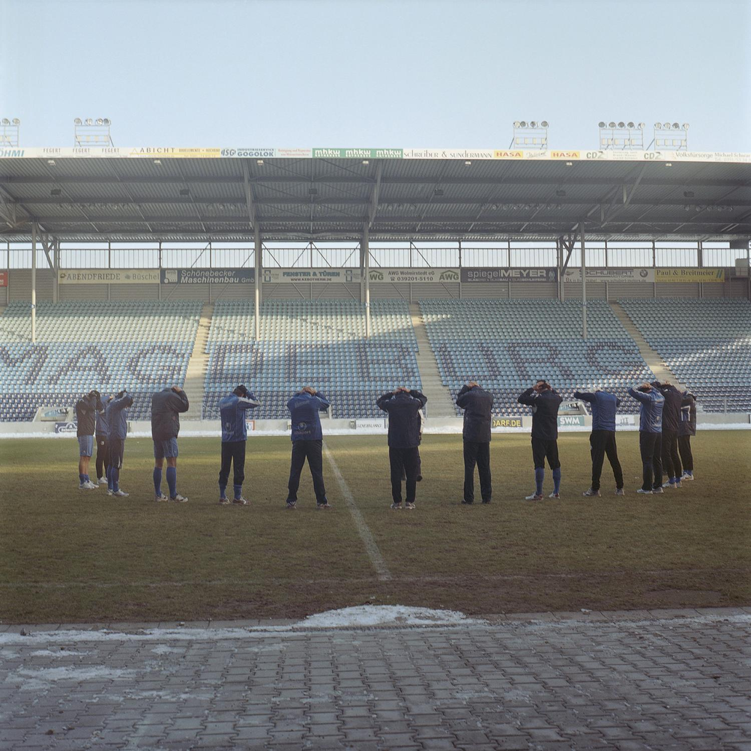 The team stretches on the main field after an official game on a cold winter Sunday, in Magdeburg.