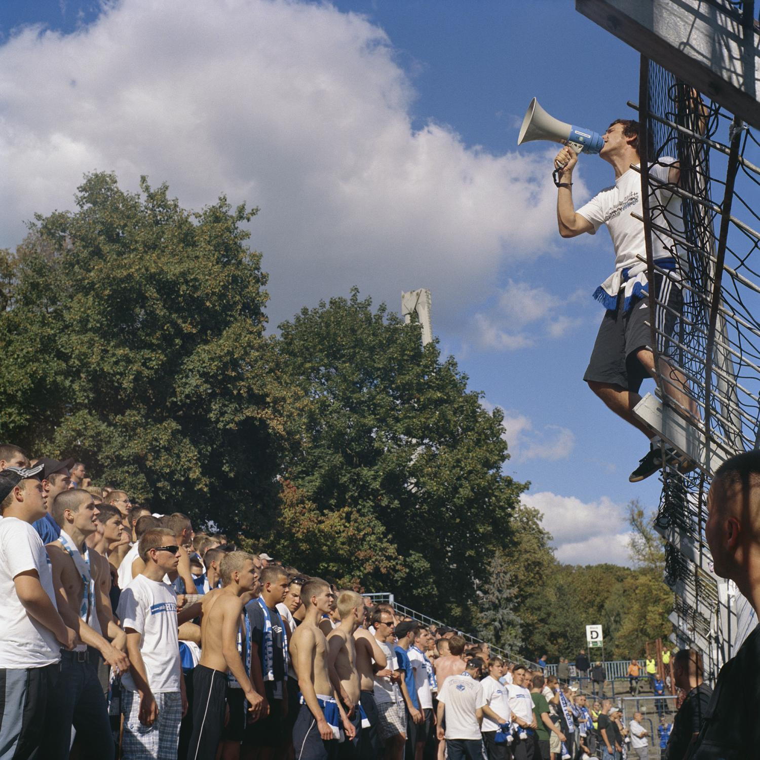 The head of the Ultras group sings on as the supporters follow, during a game of 1. FC Magdeburg in Babelsberg.