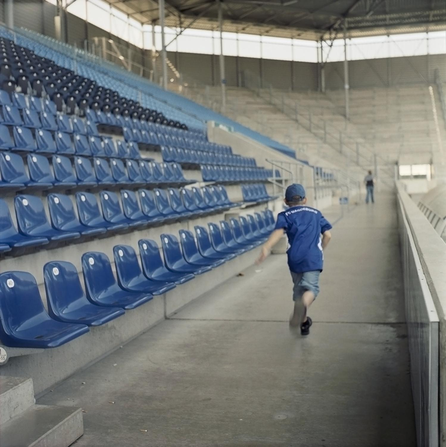 A child wearing a tricot of the 1. FC Magdeburg runs through the seats in the emtpy stadium after a game in Magdeburg.