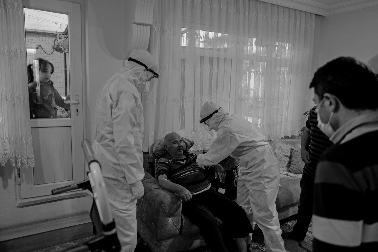 ISTANBUL, TURKEY, MAY 11- 112 Emergency Healthcare teams do the first response to a patient at home, wearing protective clothing in Küçükçekmece, ā°stanbul. The grandchildren of the sick person watch the healthcare professionals and their grandfather behind the window.