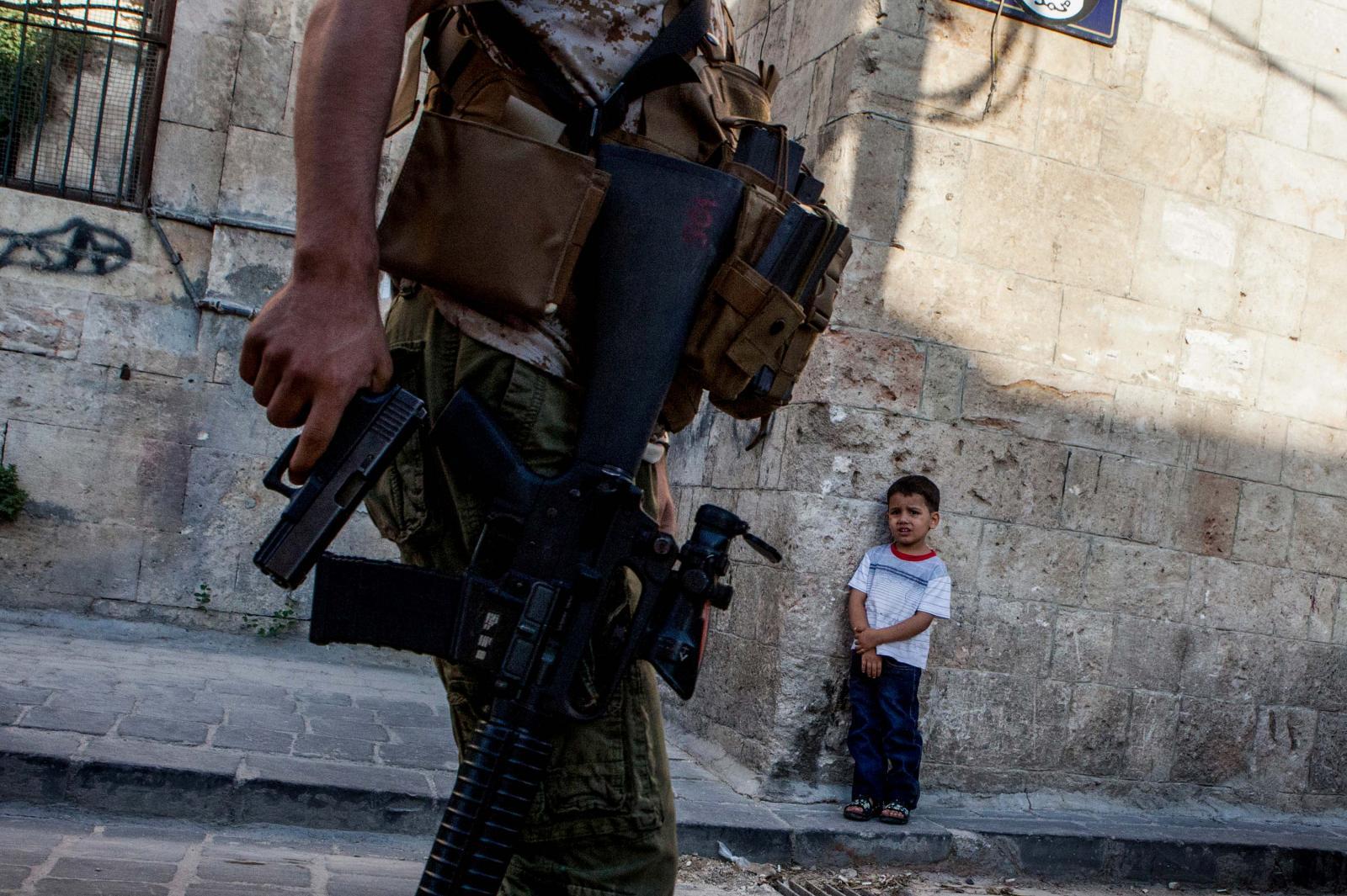 ONLAR SAVASIN COCUKLARI. Ortadogu'da bitmek bilmeyen savaslarin en buyuk magdurlari cocuklar oldu. Ic savasin yillardir devam ettigi Suriye'de, DEAS isgal ettigi Musul'da, Israā±l ablukasi altinda yasayan Gazze'de savastan en cok cocuklar etkilendi. On binlercesi daha bebek denecek yasta hayatini kaybetti, bircogu savas bolgelerinde yaralandi, yetim kaldi, bazilari buyuk umutlarla çiktigi Avrupa yolculugunda Ege'nin soguk sularinda boguldu. Silahlarin golgesinde buyumeye çalisan masum cocuklarin hikayesi. Halep'te siradan bir gun, sehir merkezinde gezen Ozgur Suriye Ordusu askerlerinin arasā±nda kalan minik bir cocuk endiseli gozlerle eli silahlā± askerlere bakā±yor. 18 Temmuz 2015 HALEP UGUR YILDIRIM/SABAH GAZETESI