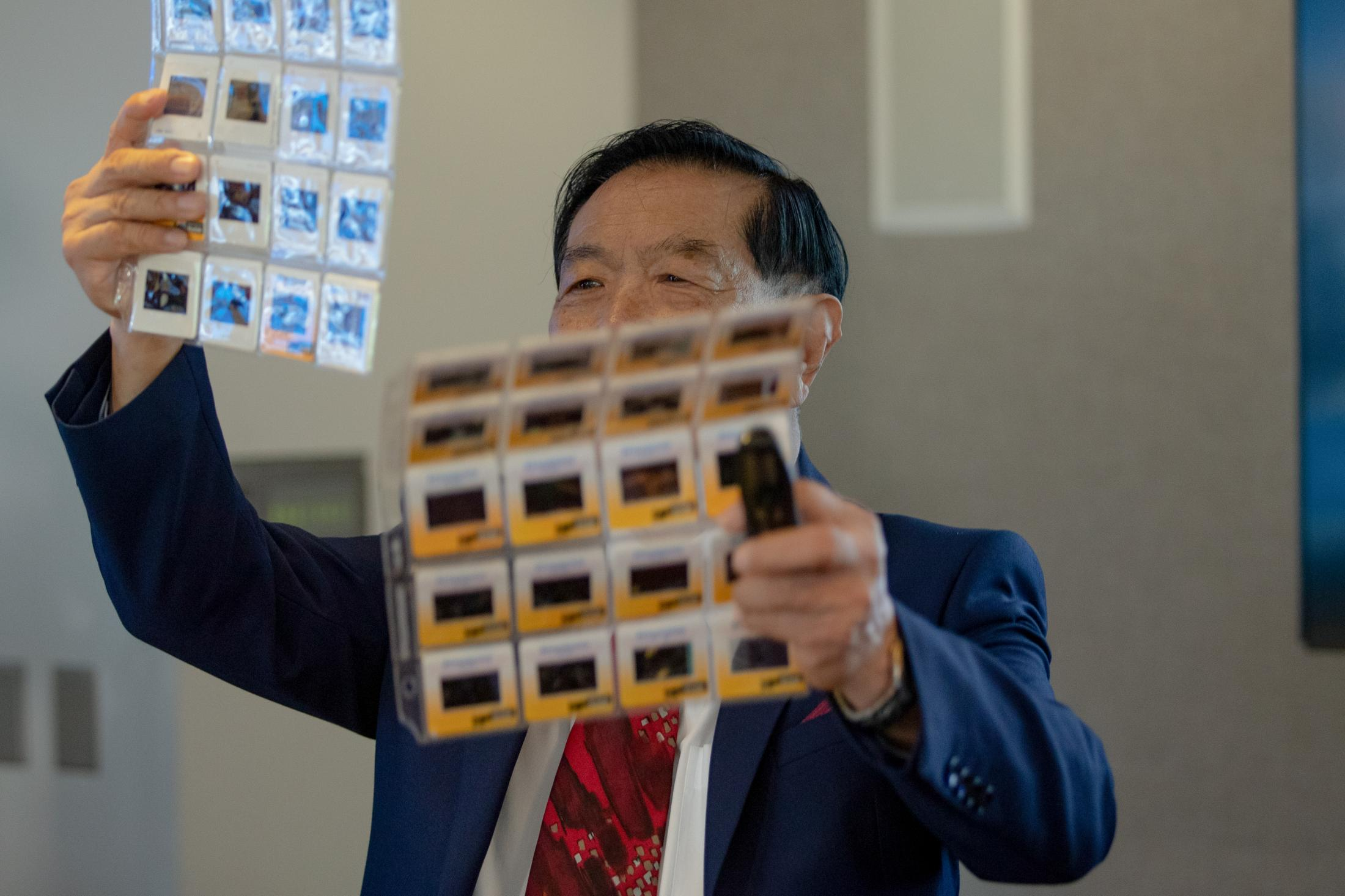 Dr. Henry Lee looks over crime scene photo slides that were handed to him after taking questions at a press conference at the University of New Haven in West Haven, CT on July 11, 2019, to defend his testimonies in court for cases that may have led to false convictions.