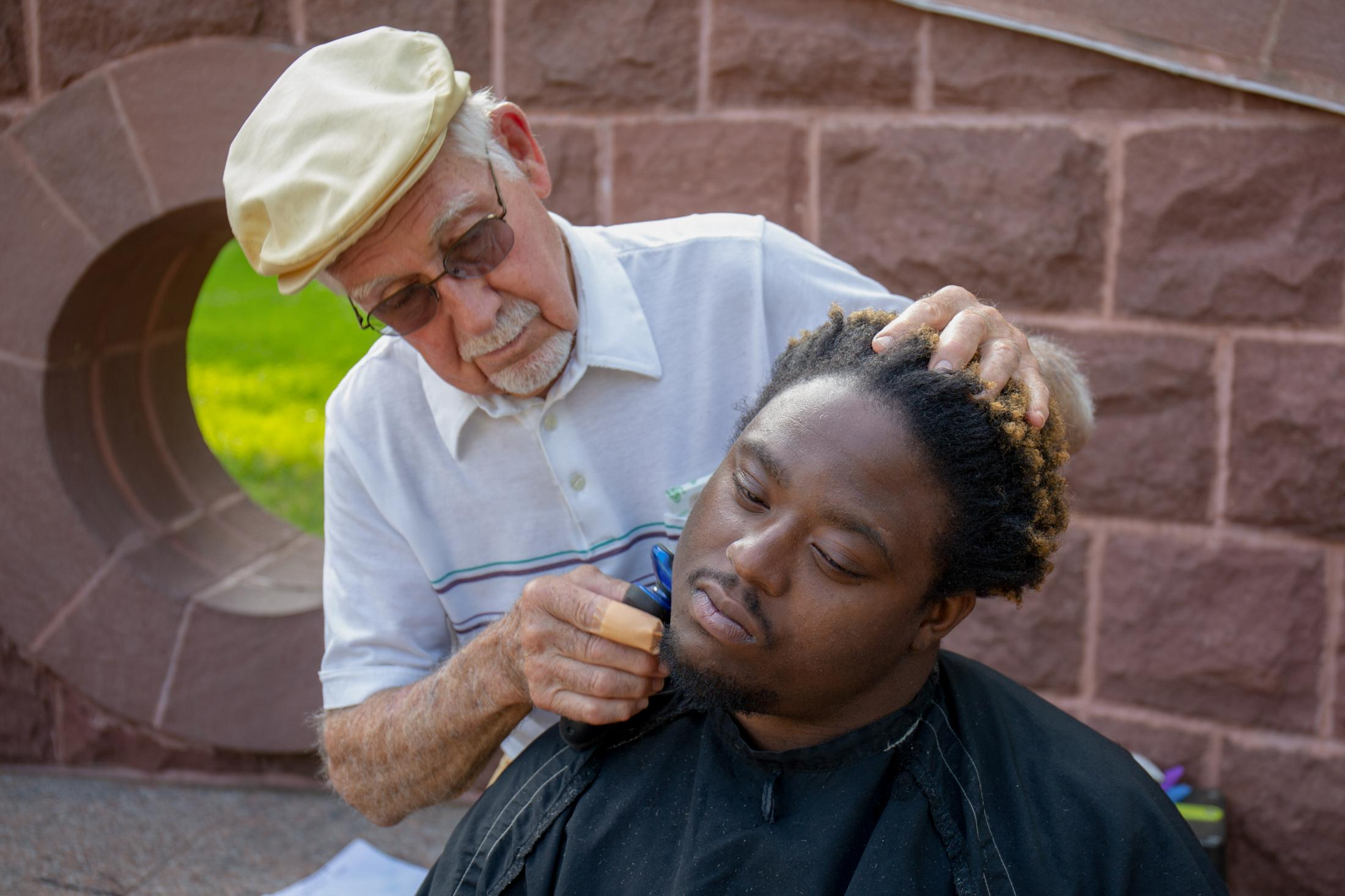 Anthony Cymerys of Hartford, CT, also known as Joe the Barber who has been giving out free haircuts for over 30 years, gives a shave and a haircut to Mark Bonner also from Hartford in Bushnell Park on May 22, 2019.