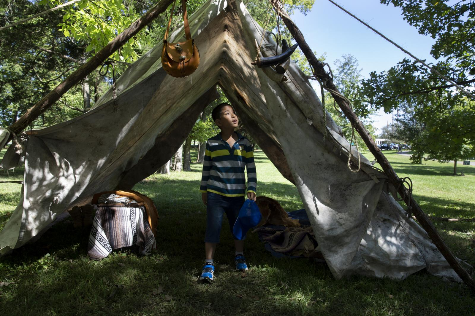 "Lucas He, 8, explores a 19th-century-style mountain man camp during Columbia's 39th annual Heritage Festival and Craft Show at Nifong Park in Columbia, Missouri. A dozen artisans and tradesmen dressed in 19th century attire, demonstrated their trades and sold their wares. Xiao Ling Guo, the boy's mother, said, ""We are newcomers, so I think it's really important for us to understand the depth of local culture."""