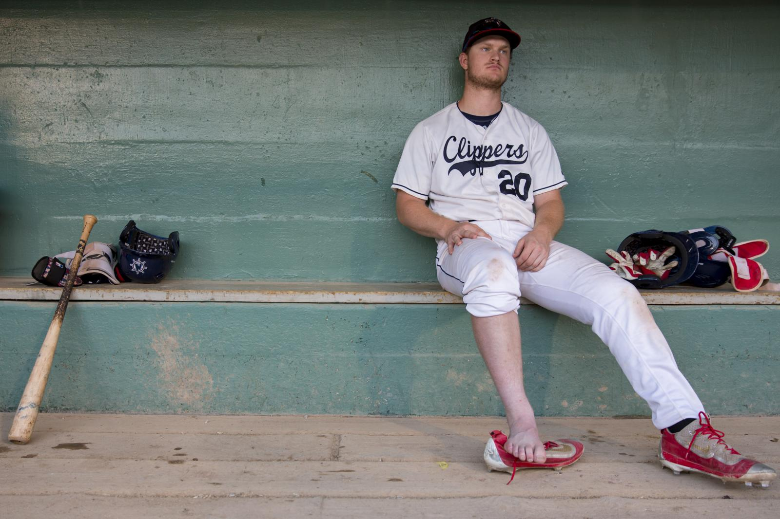 Muskegon Clippers Peter Zimmermann (20) rests in the dugout after an ankle injury on the right foot during a game against Grand River Loggers at Marsh Field in Muskegon, Michigan. Zimmermann said he was disappointed especially because his family traveled a long way from Missouri to watch the game. Loggers defeated Clippers 6-2.