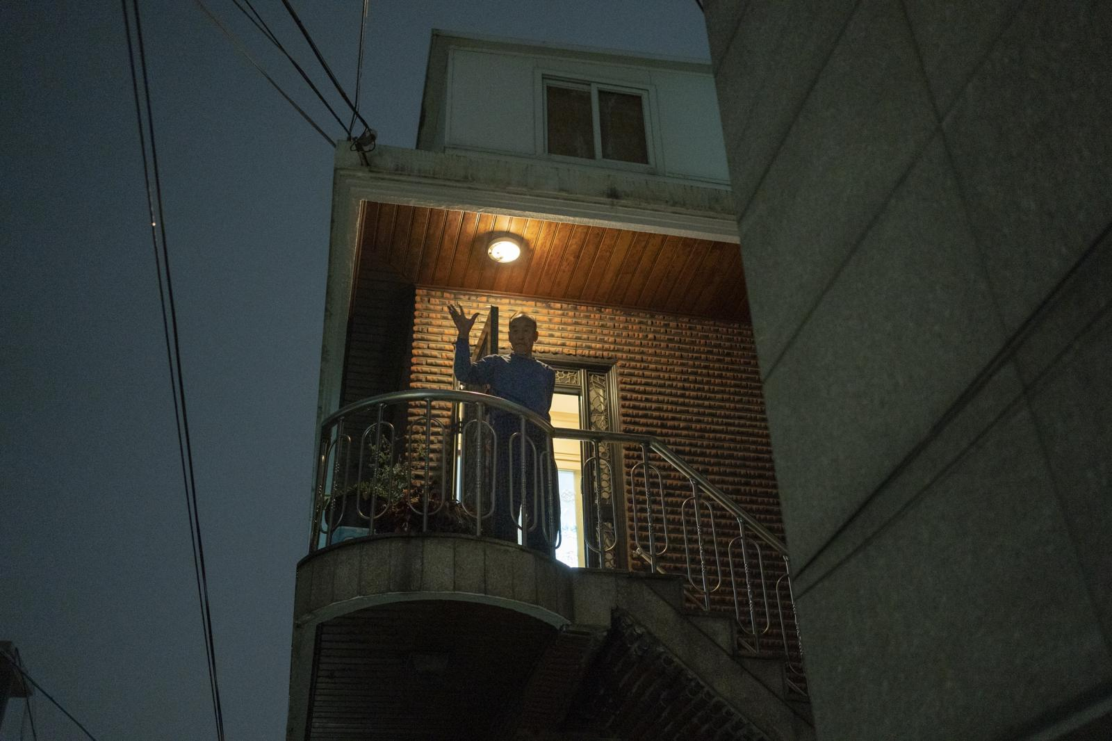 Younggil Jo waves goodbye from his porch at his home in Seoul, South Korea.