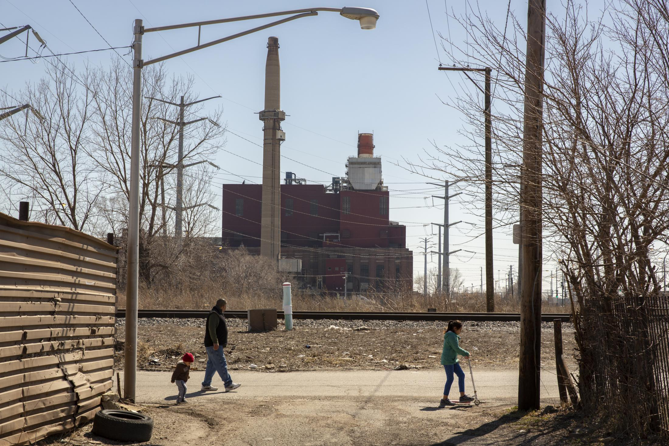 A family walks next to a railroad near Crawford Generating Station in Little Village neighborhood of Chicago. The coal power plant operated for almost 90 years, causing asthma and other respiratory issues to residents before it was forced to close in 2012 due to pressure from activists. In 2019, Hilco Redevelopment Partners gained city approval to build a 1 million-square-foot distribution center, creating concern in the community that the incoming concentration of diesel trucks will replace the former coal polluter with another harmful polluter.