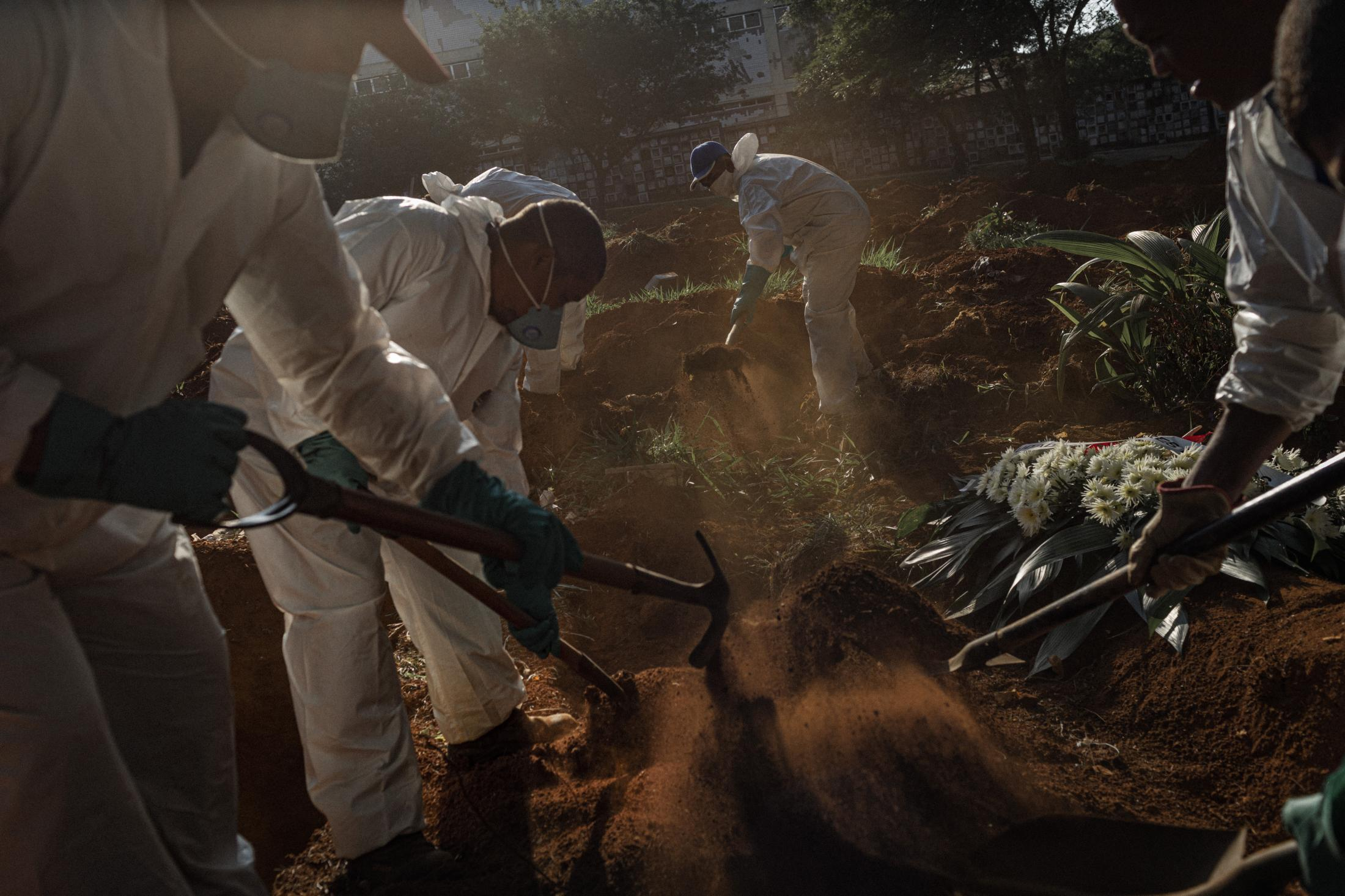 """April 21, 2020 Vila Formosa's gravediggers are usually Black men from the outskirts of São Paulo. Many commute over two hours from their homes to the cemetery. During the pandemic, 220 new workers with no previous experience in the trade were hired with precarious labor contracts to sustain the increased number of burials. """"People see us just as someone in a white suit, without feelings, who are burying their loved ones. You become invisible,"""" explains Luiz Silva, a veteran gravedigger from Vila Formosa. Aerial images of Vila Formosa, the largest cemetery in Latin America, were seen around the world at the beginning of the new coronavirus pandemic in Brazil, showing hundreds of open-air graves. The public focused on the victims of Covid-19, but little attention was paid to the silent army of gravediggers, last foot soldiers in a lost war that killed more than 200,000 people in the country by January 2020, according to the Brazilian Ministry of Health."""
