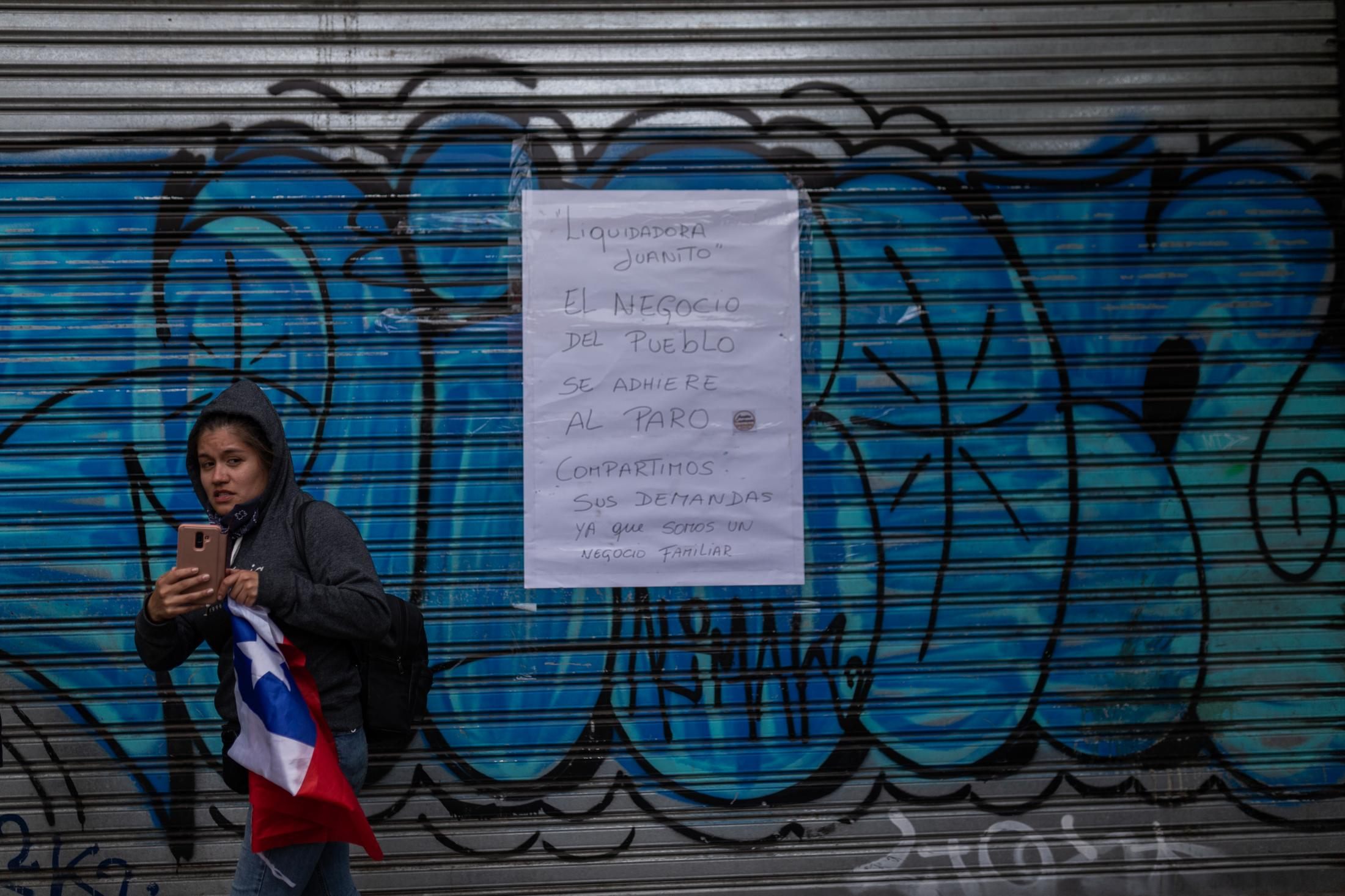 November 12, 2019. A woman records clashes between police and protesters during a day of protest in Valparaíso, Chile.