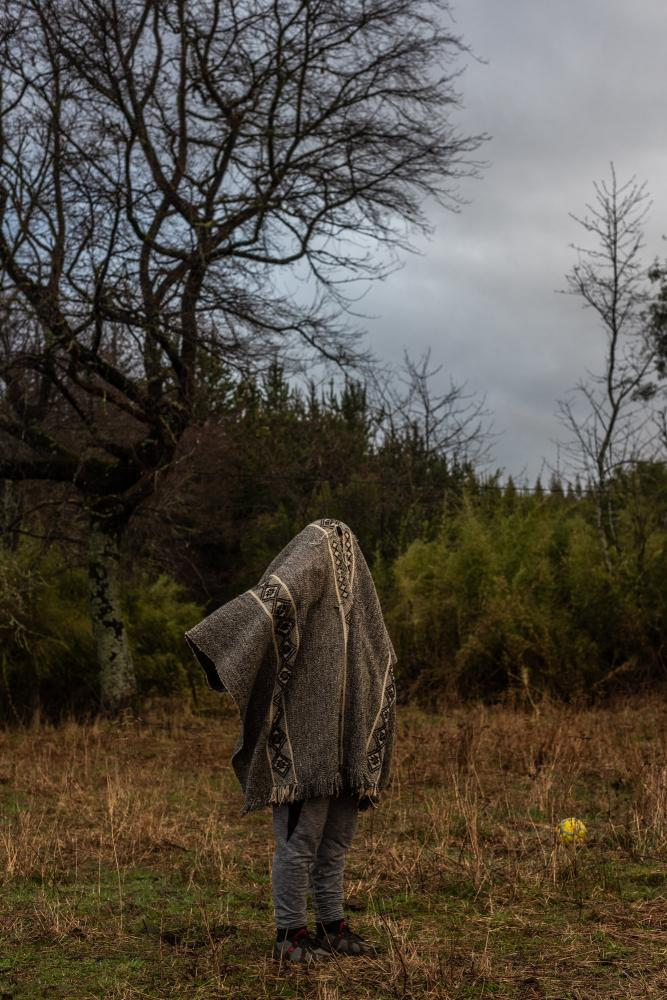 Moisés Curamil(15) son of Alberto Curamil, Mapuche political prisoner and 2019 Goldman environmental prize, which he received in jail. Here, Moisés is fitting a traditional poncho or manta, Mapuche traditional warm clothing. Curacautín, Araucanía region, Chile. August 11th, 2019.