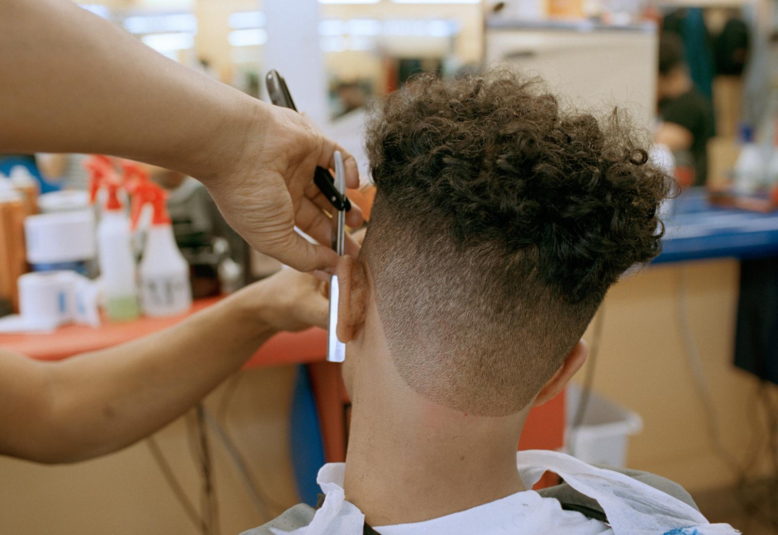 Ahmed Alzandhani gets a medium skin fade the day before a soccer match at a Dominican barbershop in the Flatbush neighborhood of Brooklyn, New York.