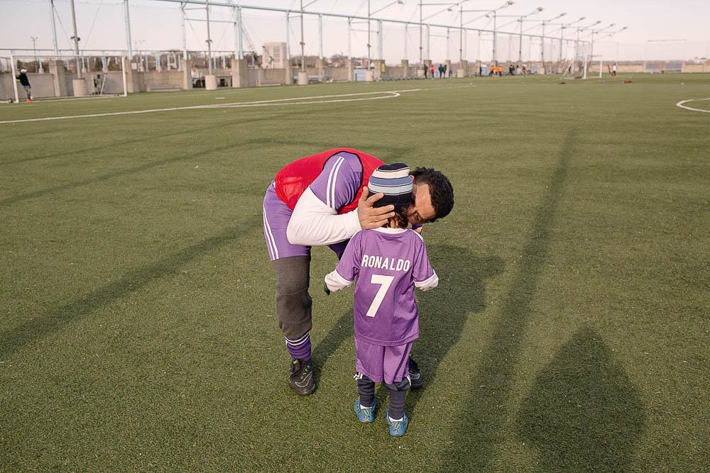 A member of the Yemen United Soccer Team kisses his son who is watching him on the sidelines during a training session at Brooklyn Bridge Park Soccer Field in Brooklyn, New York