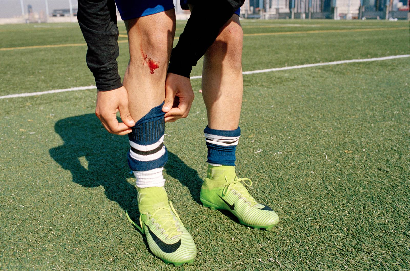 Atiff Rageh fixes his socks after getting a cleat to the knee cap during a training session with the Yemen United Soccer Team in Brooklyn, New York.