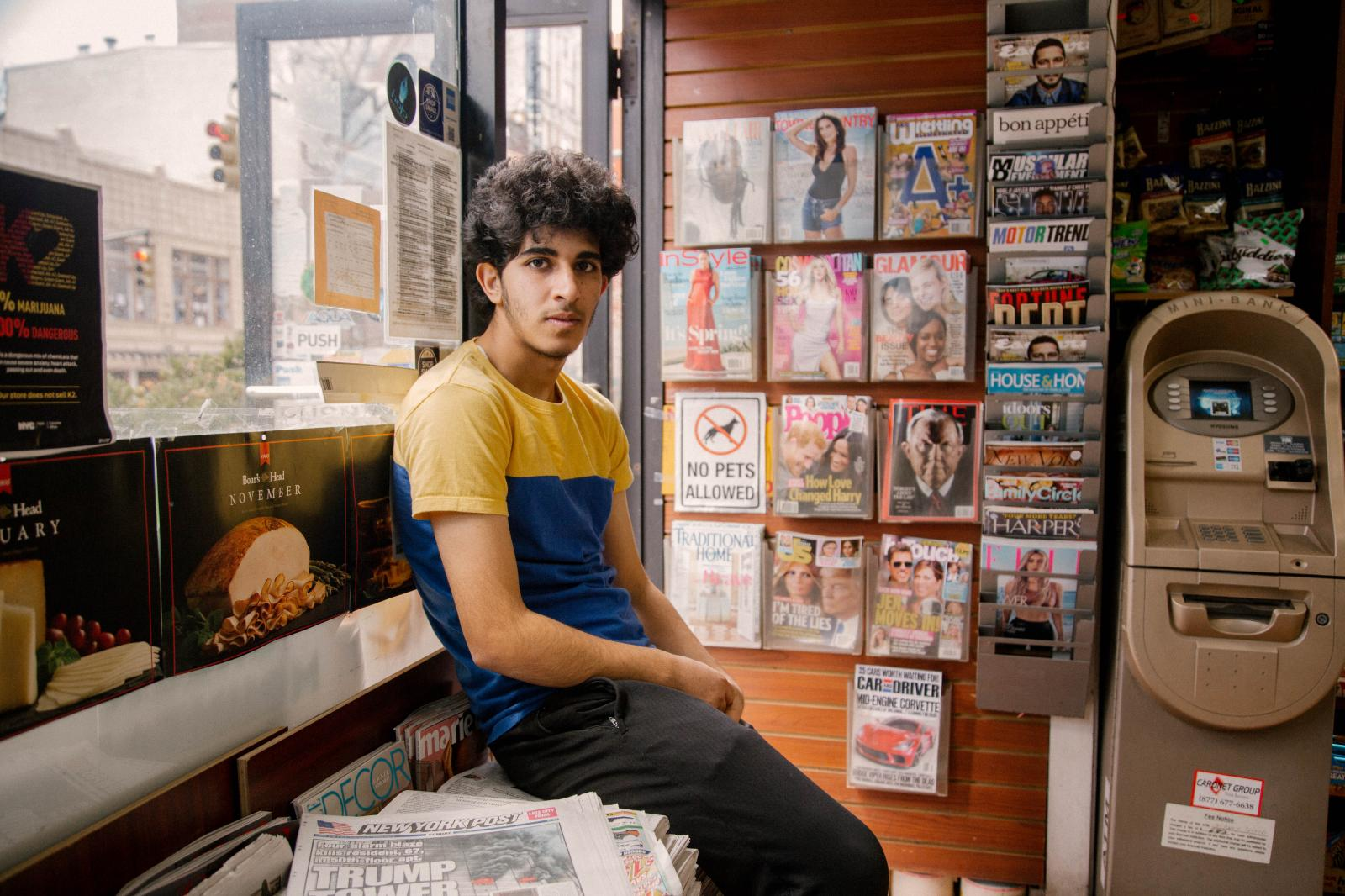 Osama Alsahybi, 20, sits in his brother's deli in the Brooklyn Heights neighborhood of Brooklyn, New York. Osama has been in the U.S. for just under two years. Having zero English knowledge prior to coming to the US, he now speaks easily, laughs often and has made friends with all the regular customerrs who enter into the deli. To then, he's known simply as Oz.
