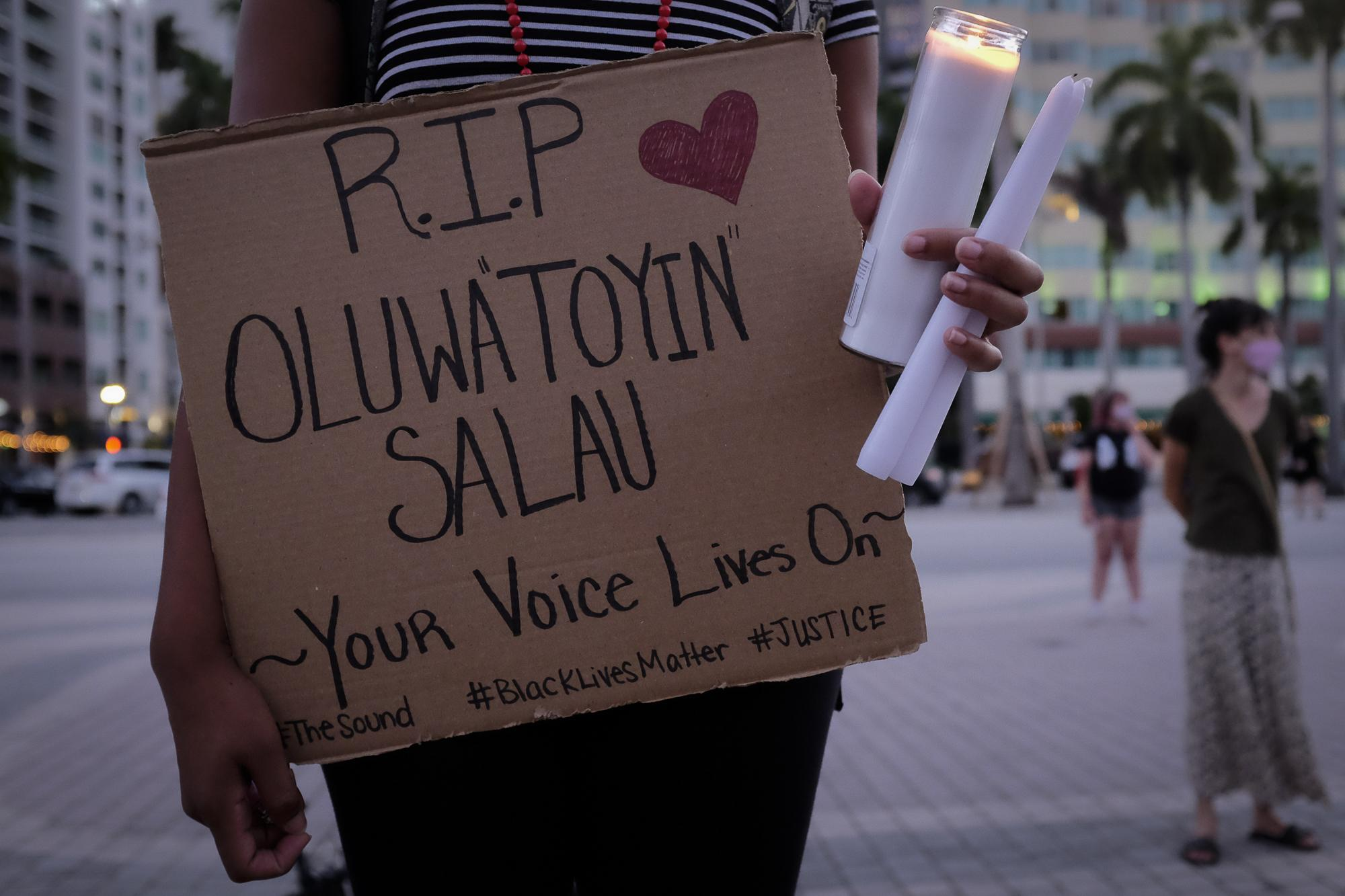 A woman holds a sign and candles as she attends a vigil for slain black activist Oluwatoyin Salau, in Downtown Miami, Florida, U.S., June 16, 2020. REUTERS/Marco Bello