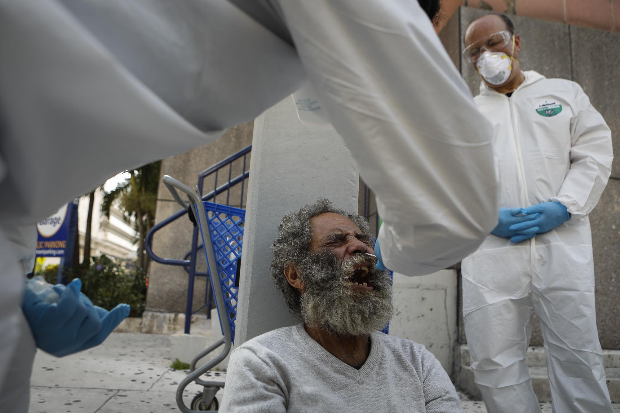 A homeless man reacts as a worker uses a swap to collect a sample during a Miami-Dade County testing operation for the coronavirus disease (COVID-19), in downtown Miami, Florida, U.S., April 16, 2020. REUTERS/Marco Bello