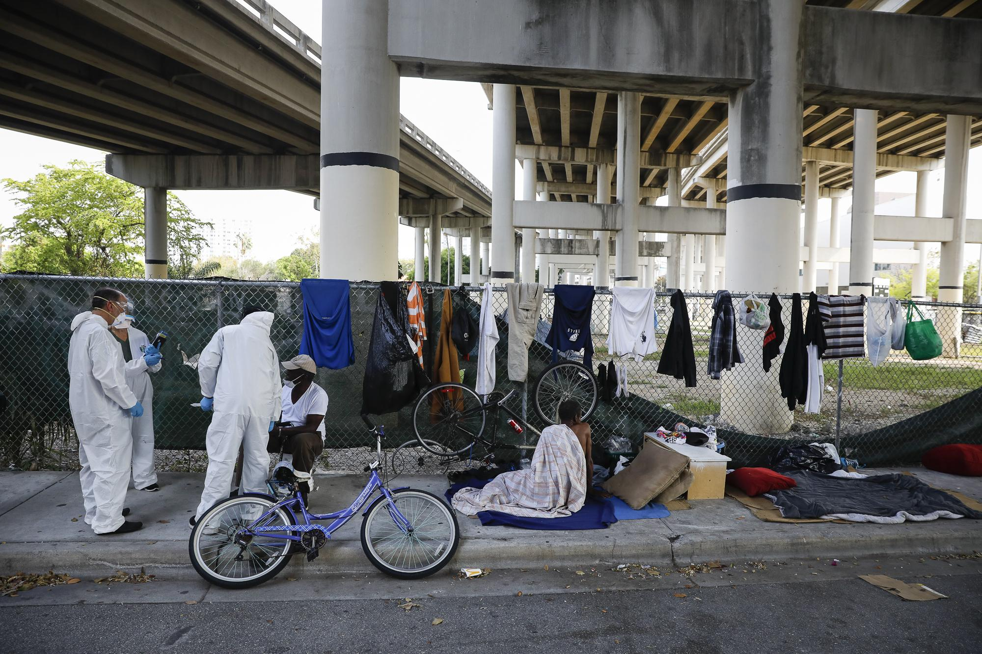Workers talk with a homeless man during a Miami-Dade County testing operation for the coronavirus disease (COVID-19), in downtown Miami, Florida, U.S., April 16, 2020. REUTERS/Marco Bello