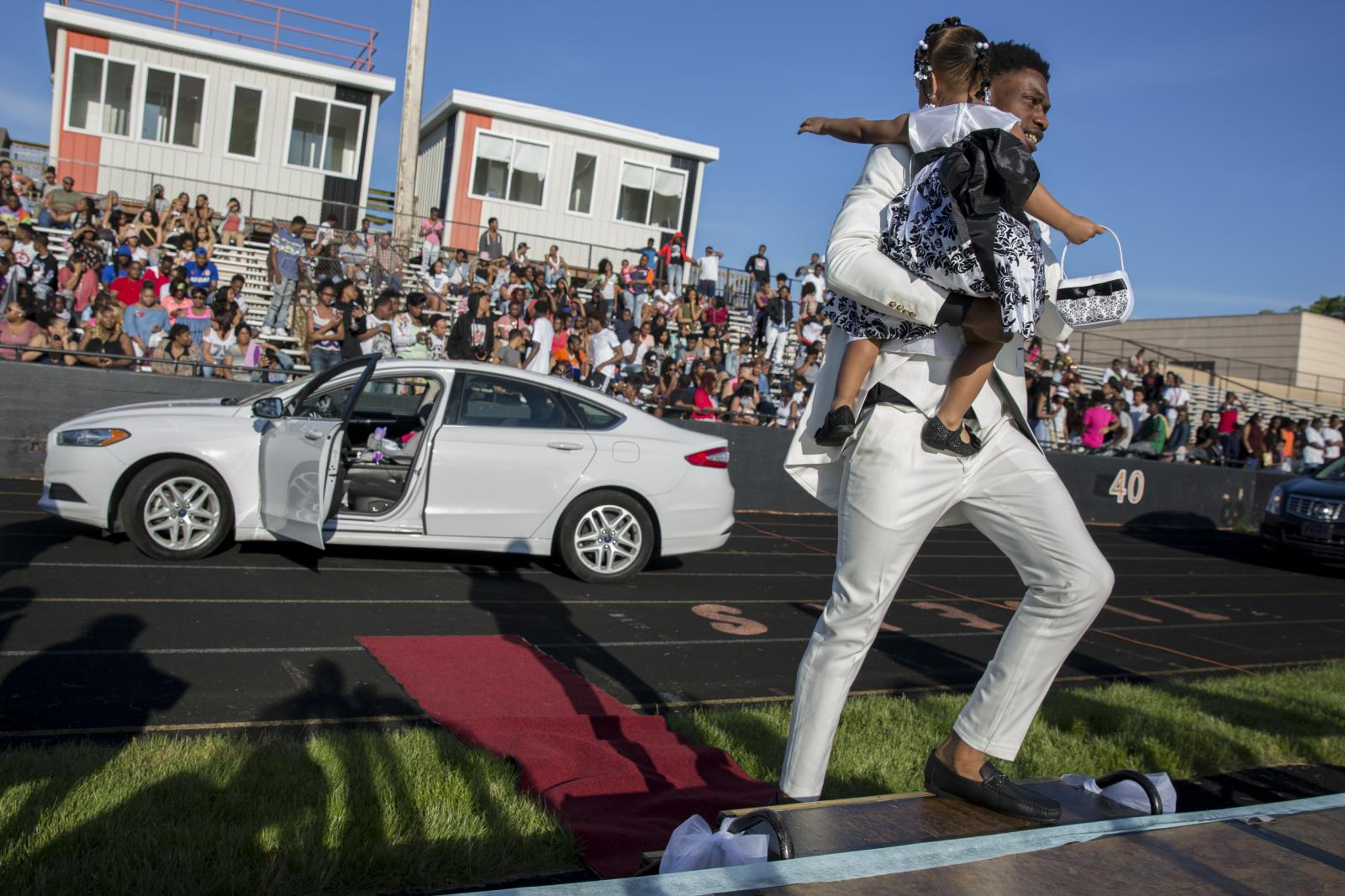 Javonte Kendrick carries his niece Monyae Helms, 1, to the stage as their names were announced during Muskegon Heights Academy's traditional pre-prom Showoff in Muskegon Heights, Michigan. A longstanding tradition, Showoff involved 40 students and their dates driving up in front of a platform on the high school football field before heading to the prom.