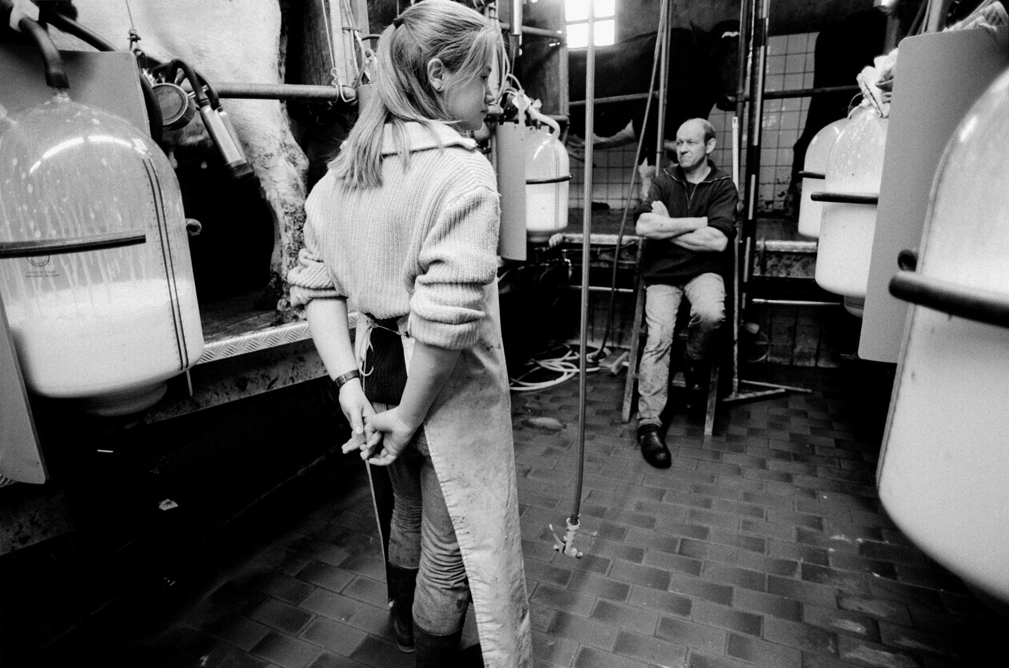 Mirjam wants to become a farmer and milk cows. She is a student at the agricultural school. During her weekly apprenticeship she is learning the milking process on the farm of Piet Verhoef. Nieuwerbrug, The Netherlands. February 1995.