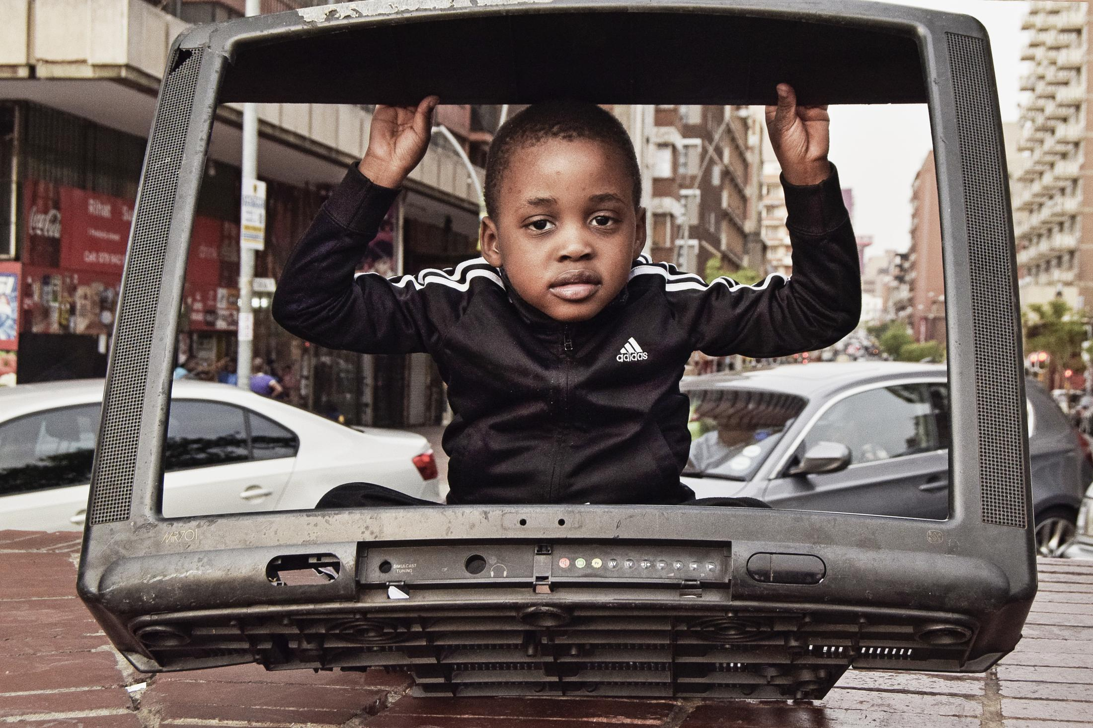 "A young boy plays in the frame of broken television set at Pretoria street in Hillbrow on Sept 15, 2015. Pretoria street is one of the most famous street in Hillbrow with many businesses both formal and informal. Hillbrow is an inner city residential neighbourhood of Johannesburg known for its high level of populationdensity, unemployment, poverty, prostitution and crime. This project ""Transition"" looks at the short and long-term changes that have occured and continue to occur in the area, and the effect of life here on the people."""