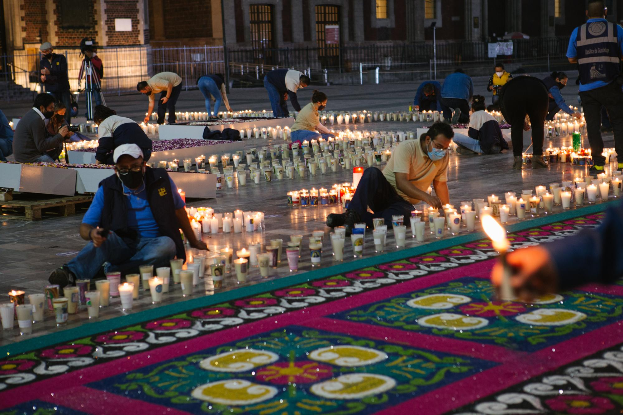 Employees of the Basilica of Our Lady of Guadalupe in Mexico City, Mexico light approximately 15,000 candles left by pilgrims ahead of its closure due to the COVID-19 pandemic. The candles are meant as a symbol of their presence.