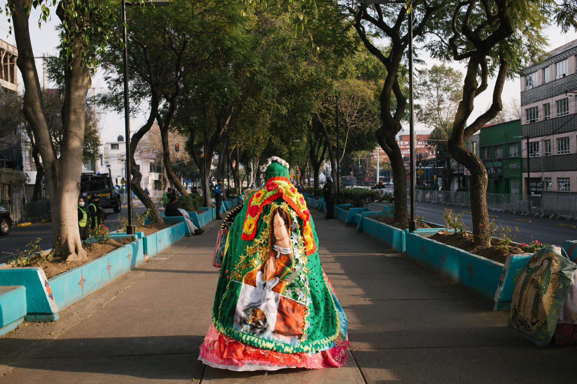 Ana Rita Ruedas Arana, 64, sings Las Mañanitas, the Mexican version of Happy Birthday, to the Virgin of Guadalupe on Feast Day on the street leading up to the Basilica of Our Lady of Guadalupe in Mexico City, Mexico. The basilica and surrounding streets are closed due to the COVID-19 pandemic.